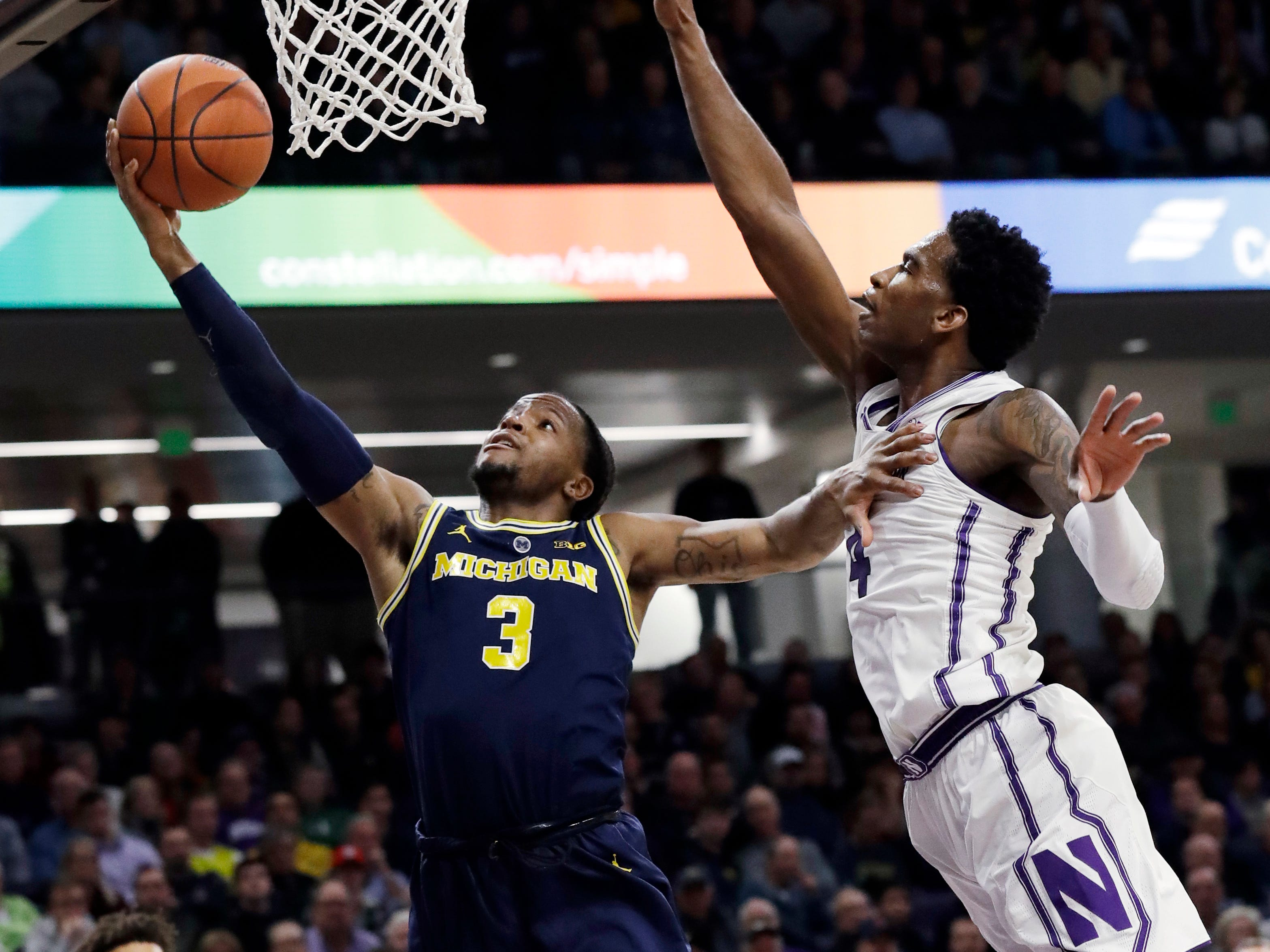 Michigan guard Zavier Simpson shoots against Northwestern forward Vic Law during the first half Tuesday, Dec. 4, 2018, in Evanston, Ill.