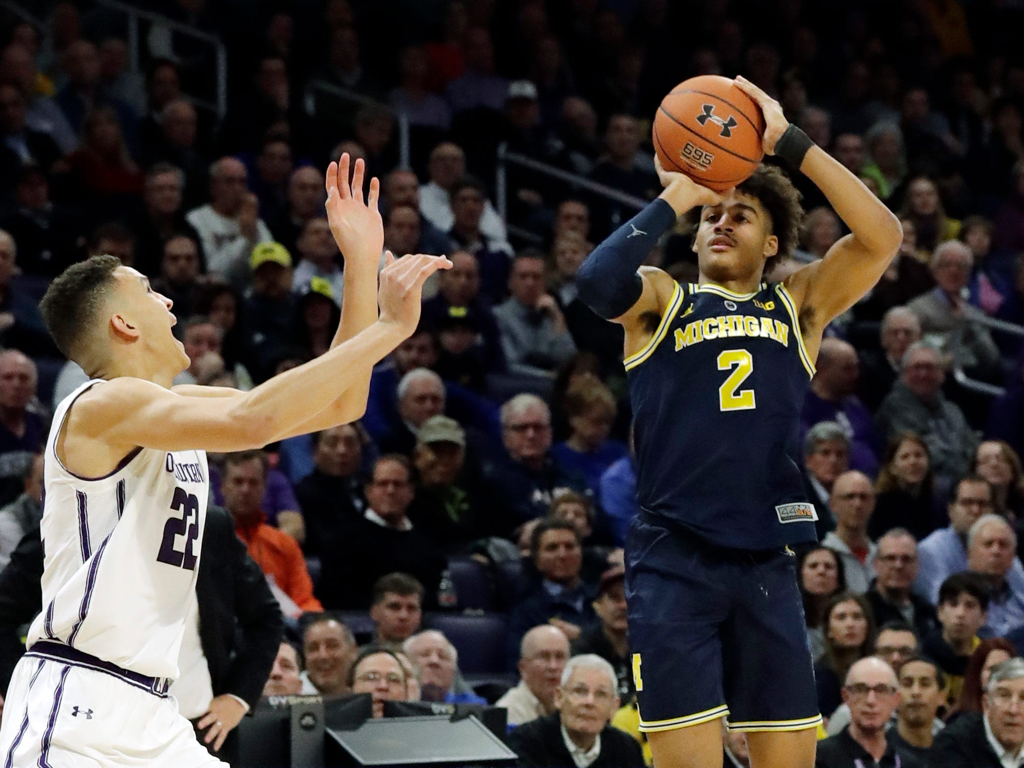 Michigan guard Jordan Poole shoots against Northwestern forward Pete Nance during the first half Tuesday, Dec. 4, 2018, in Evanston, Ill.