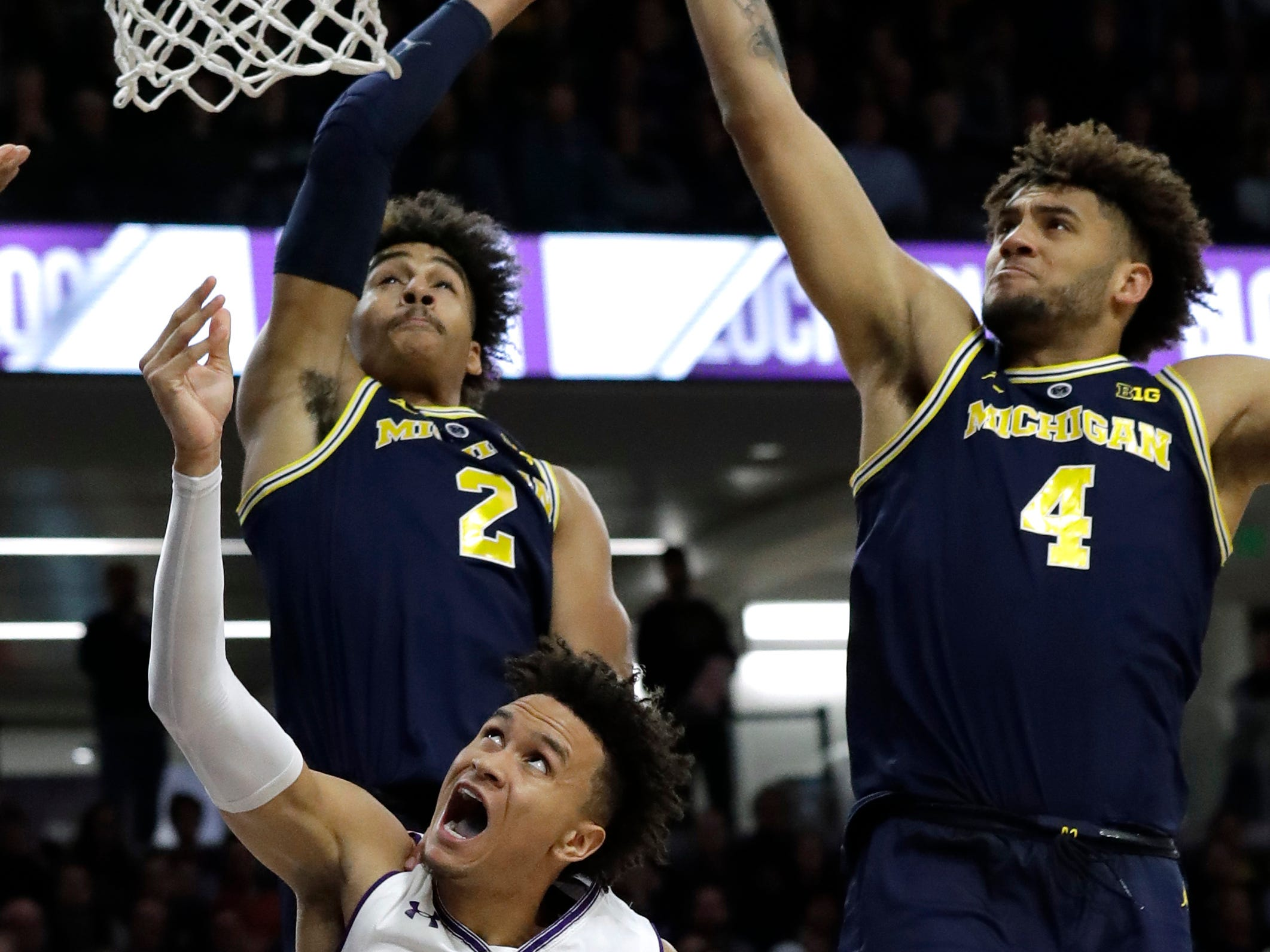 Northwestern forward A.J. Turner shoots against Michigan guard Jordan Poole (2) and forward Isaiah Livers during the second half of U-M's 62-60 win on Tuesday, Dec. 4, 2018, in Evanston, Ill.