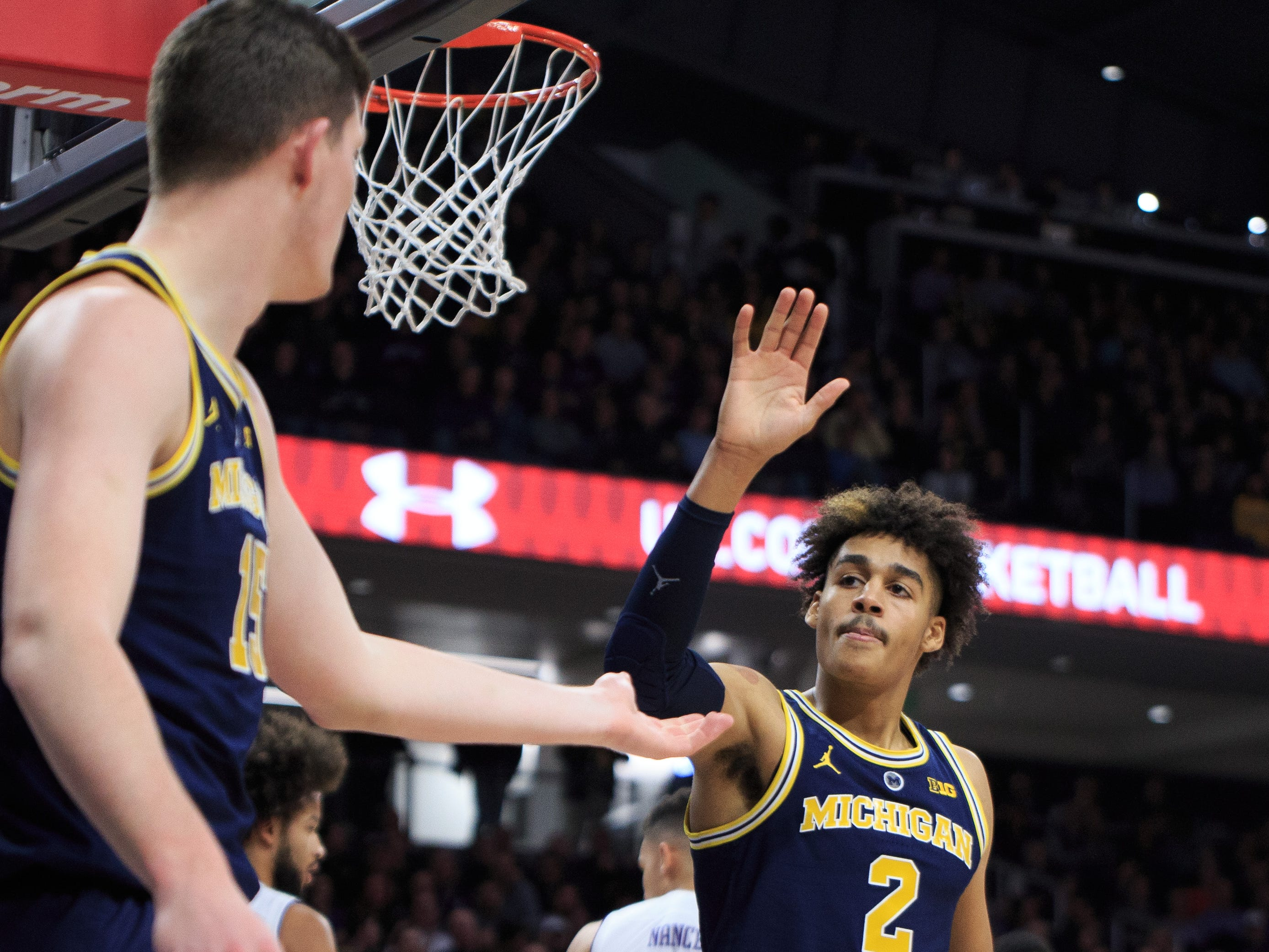 Michigan's Jordan Poole, right, celebrates with Jon Teske against Northwestern in the first half at Welsh-Ryan Arena on Dec. 4, 2018 in Evanston, Ill.