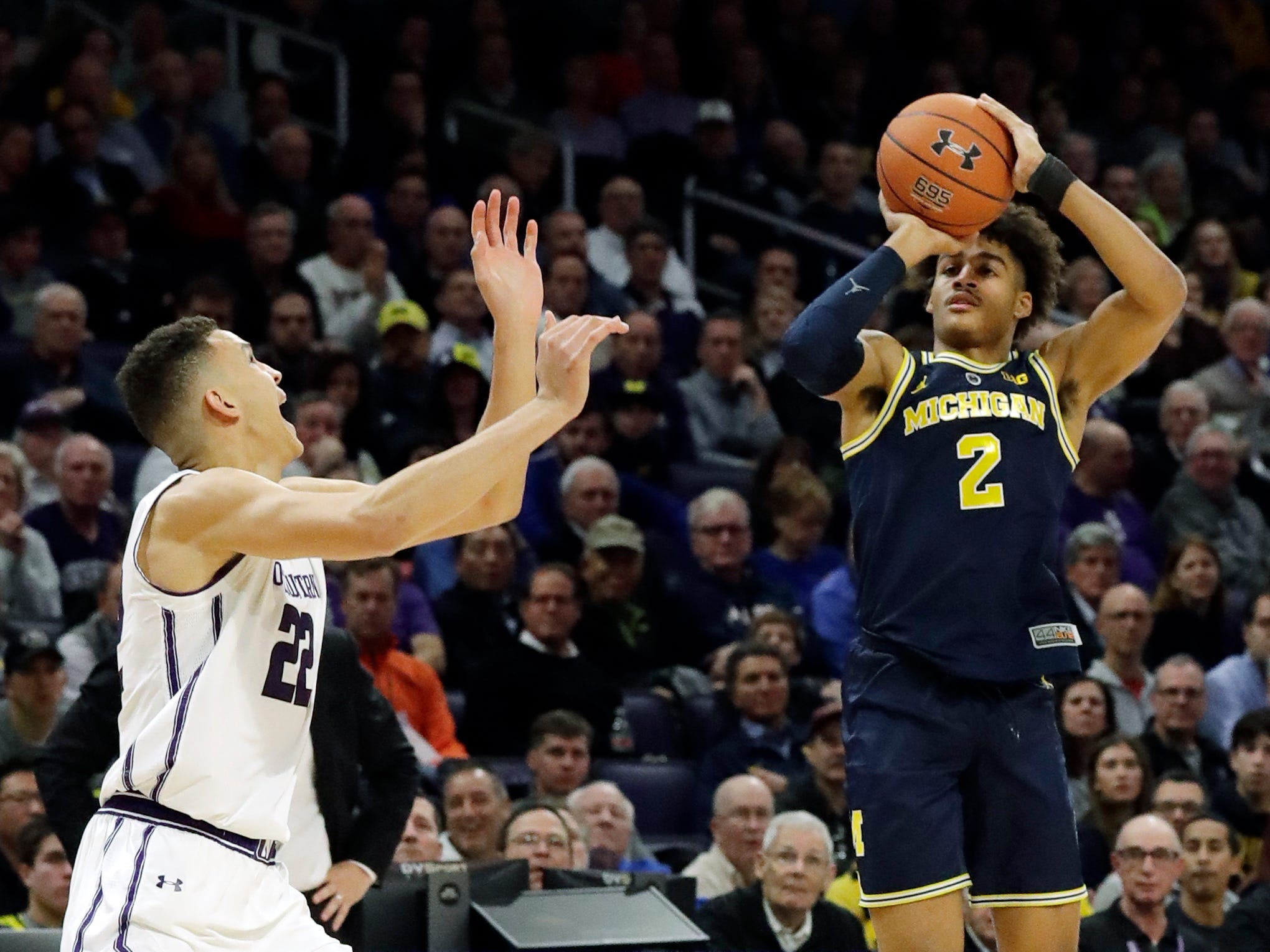 Michigan guard Jordan Poole, right, shoots against Northwestern forward Pete Nance during the first half.