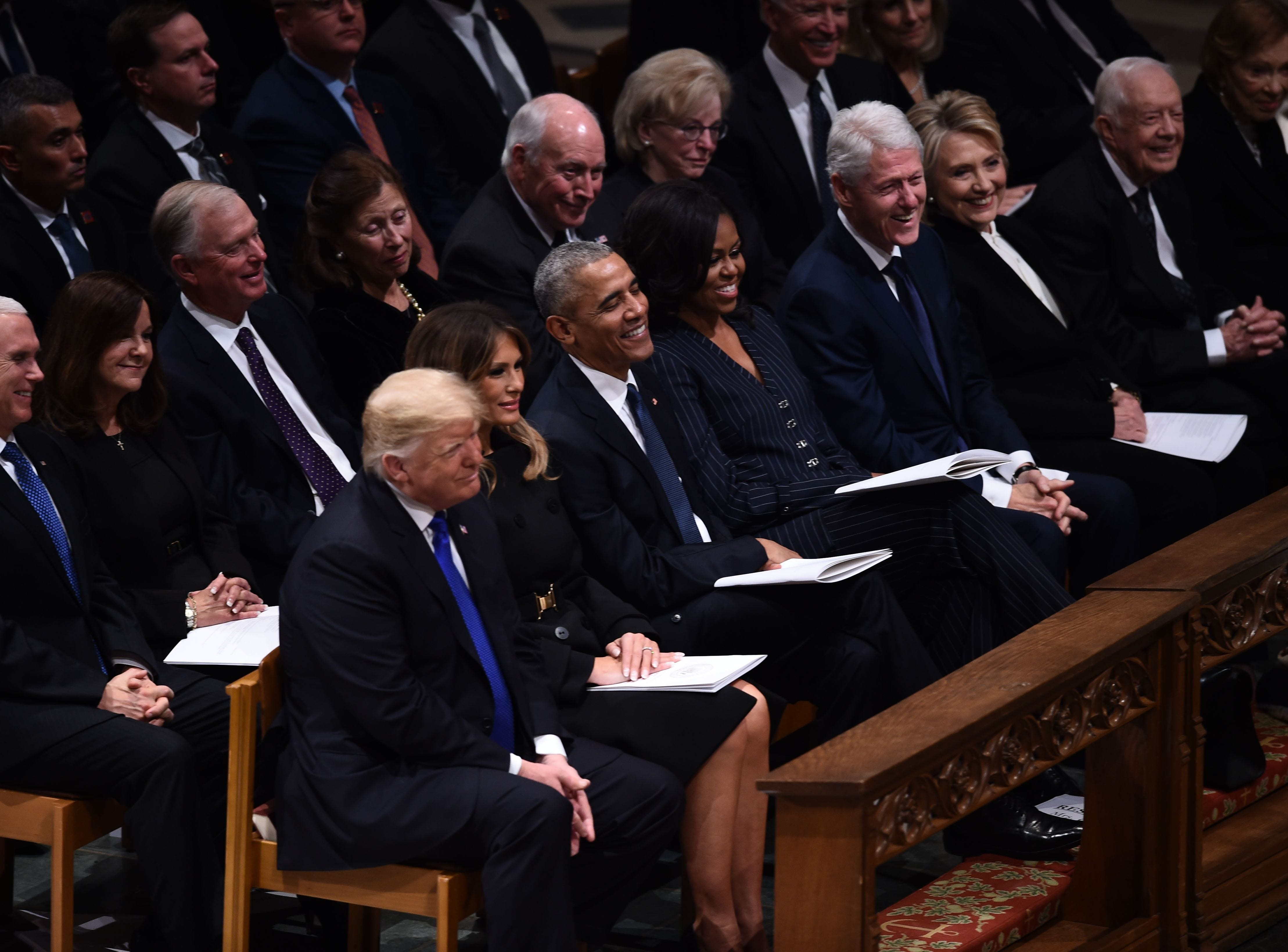 President Donald Trump, first lady Melania Trump, former President Barack Obama, former first lady Michelle Obama, former President Bill Clinton, former first lady Hillary Clinton, former President Jimmy Carter, and former first lady Rosalynn Carter smile during remarks at  the state funeral of former President George H.W. Bush. Behind them are Vice President Mike Pence and former vice presidents Dan Quayle, Dick Cheney, Joe Biden and their wives.