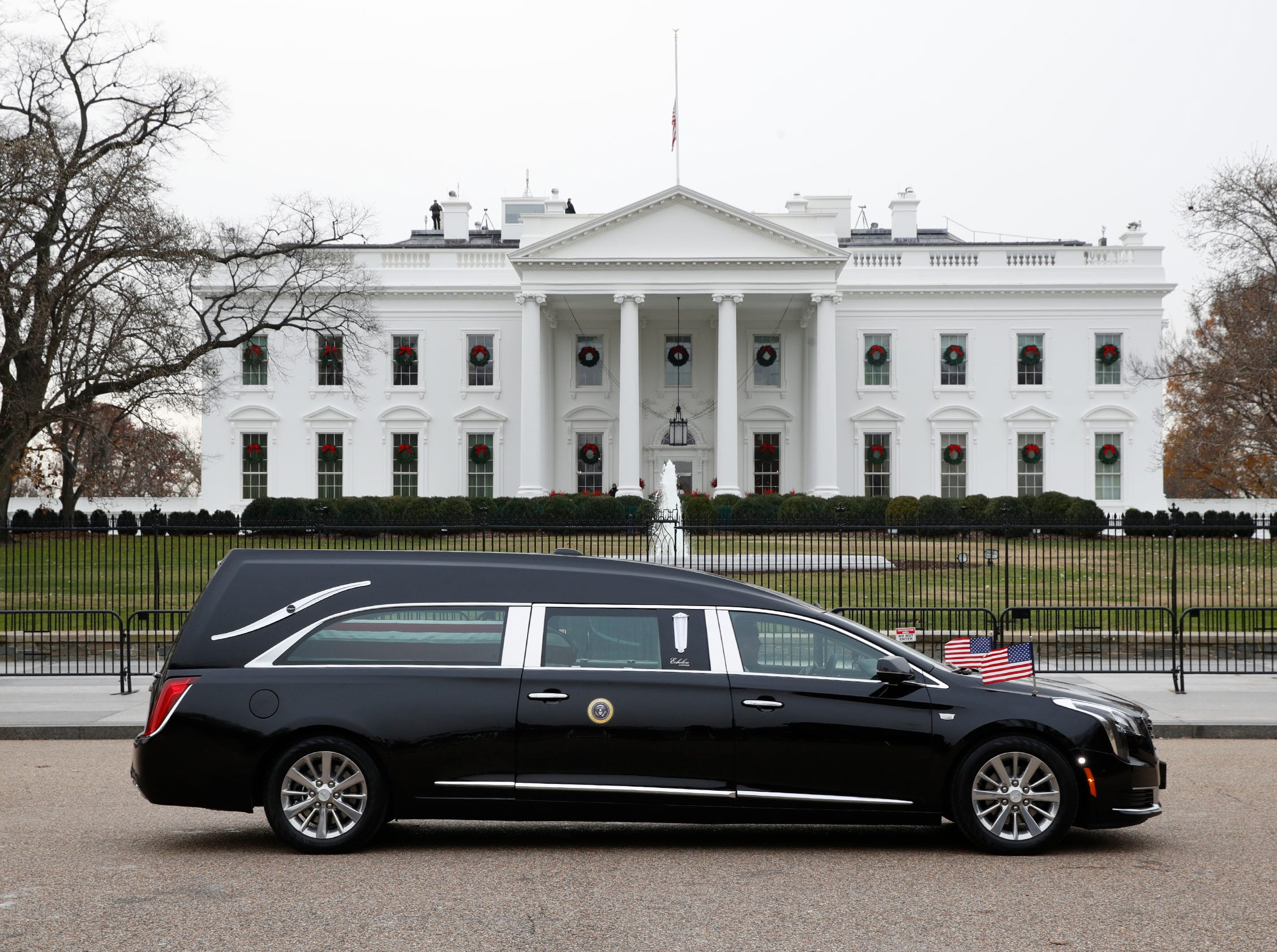 The hearse carrying the flag-draped casket of former President George H.W. Bush passes by the White House from the Capitol, heading to a State Funeral at the National Cathedral.