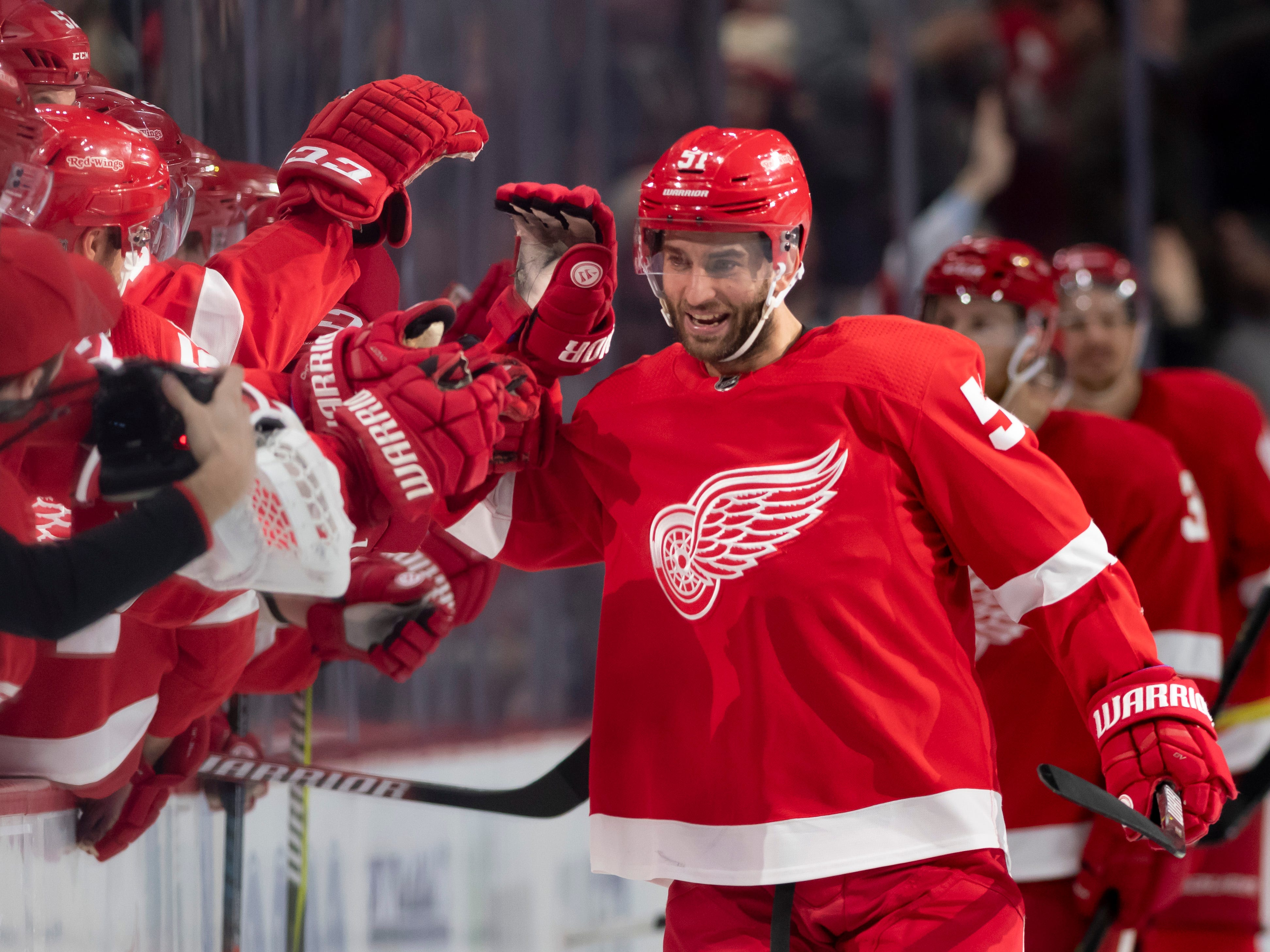 Detroit center Frans Nielsen gets high fives from his teammates after scoring a hat trick in the second period.