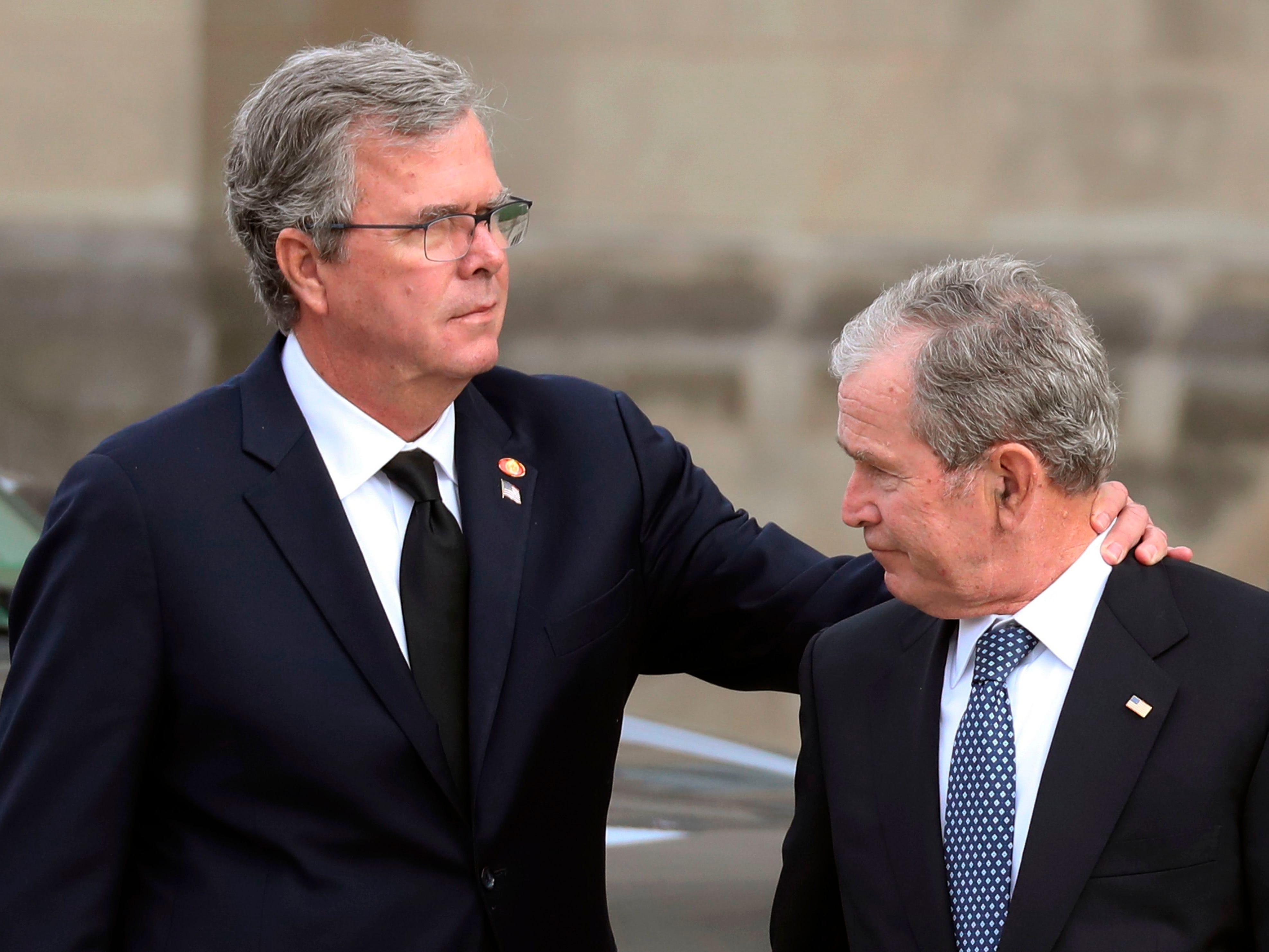 Former President George W. Bush, right, and his brother, former Florida Gov. Jeb Bush, arrive for the funeral for their father, former President George H. W. Bush, at the National Cathedral.