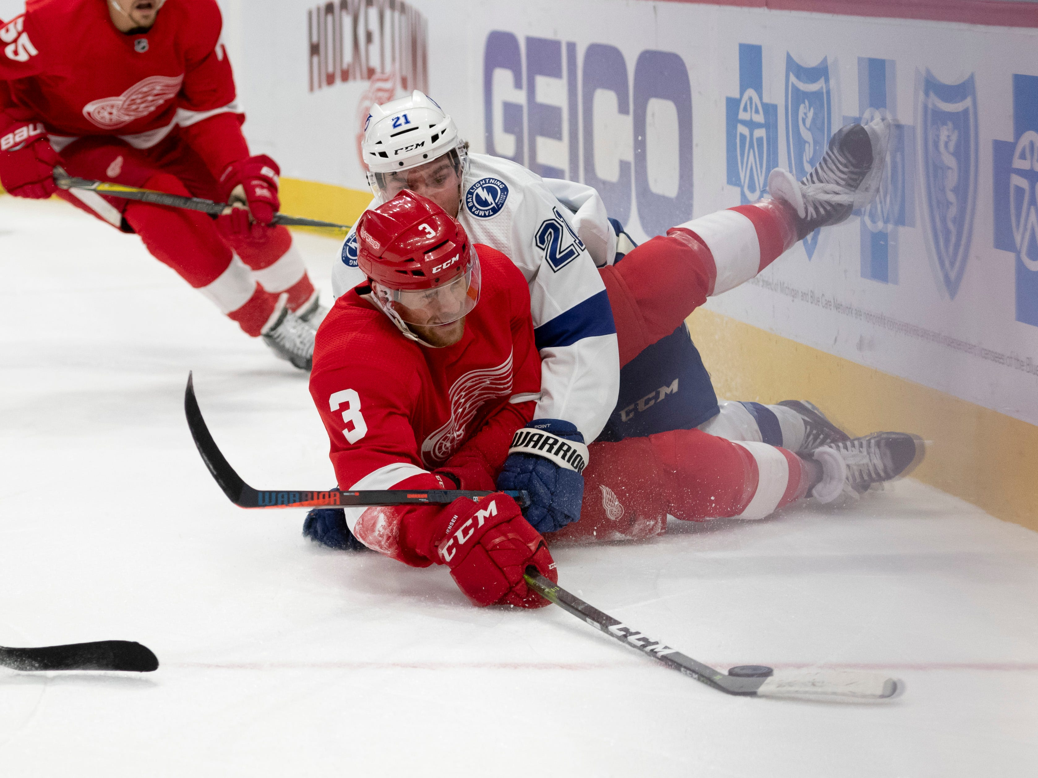 Detroit defenseman Nick Jensen and Tampa Bay center Brayden Point hit the ice while battling for the puck in the second period.