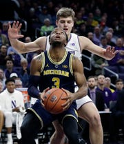 Michigan guard Zavier Simpson  looks to the basket as Northwestern forward Miller Kopp guards during the first half on Dec. 4.