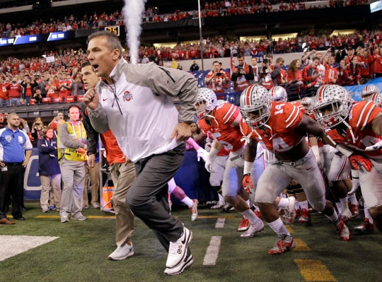 In this Dec. 6, 2014 photo, Ohio State head coach Urban Meyer runs onto the field with his team at the start of the Big Ten Conference championship game against Wisconsin.