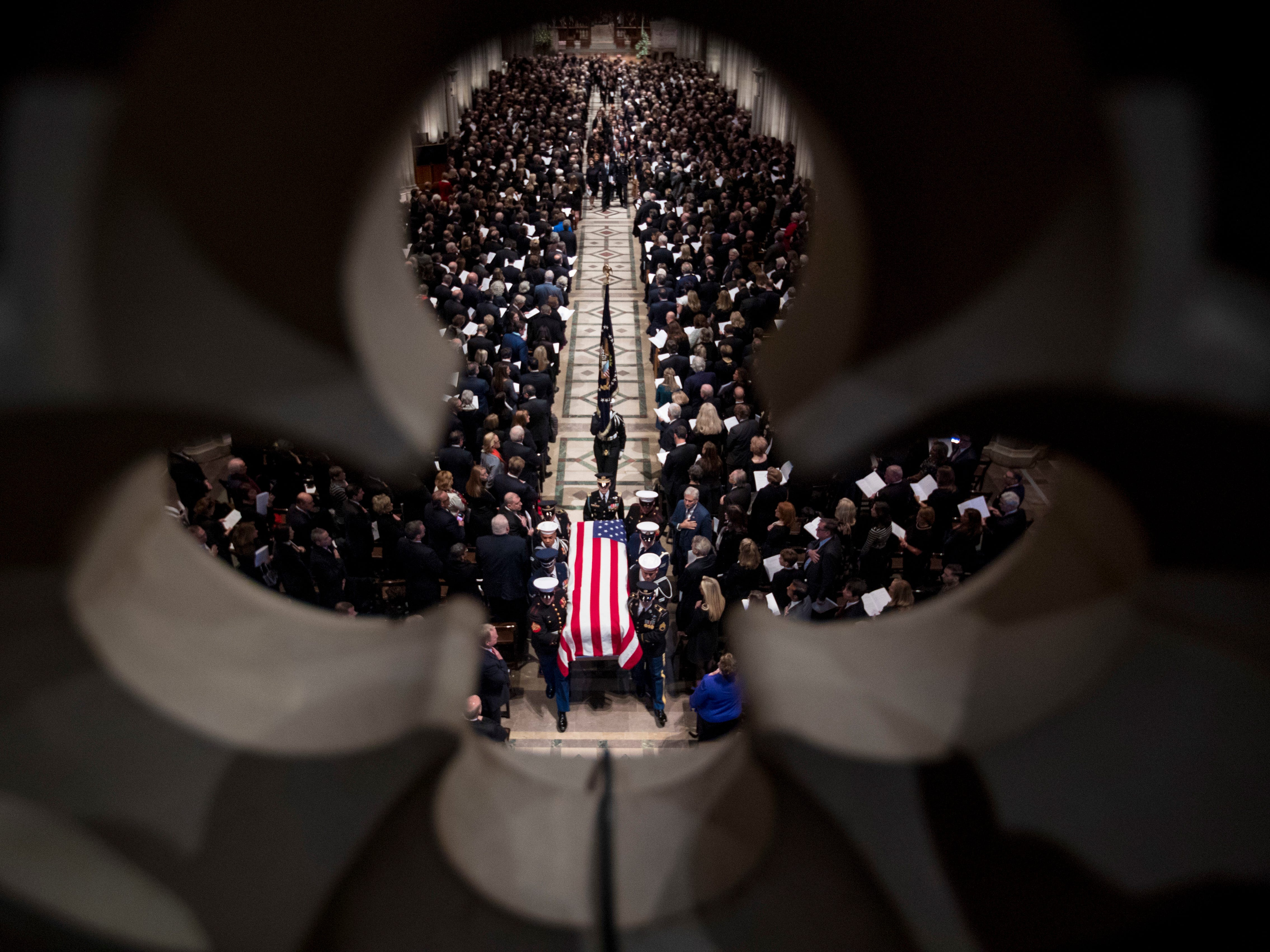 The flag-draped casket of former President George H.W. Bush is carried out  of the National Cathedral by a military honor guard.
