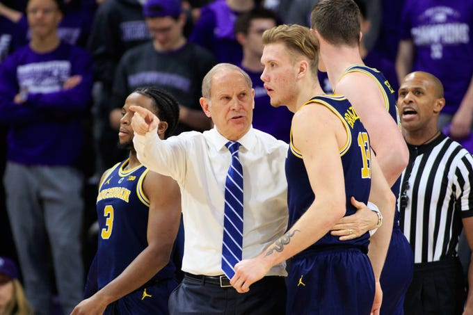 Michigan Wolverines head coach John Beilein talks to Ignas Brazdeikis #13 during a time out in the game against the Northwestern Wildcats at Welsh-Ryan Arena on December 4, 2018 in Evanston, Illinois. Michigan wins, 62-60.
