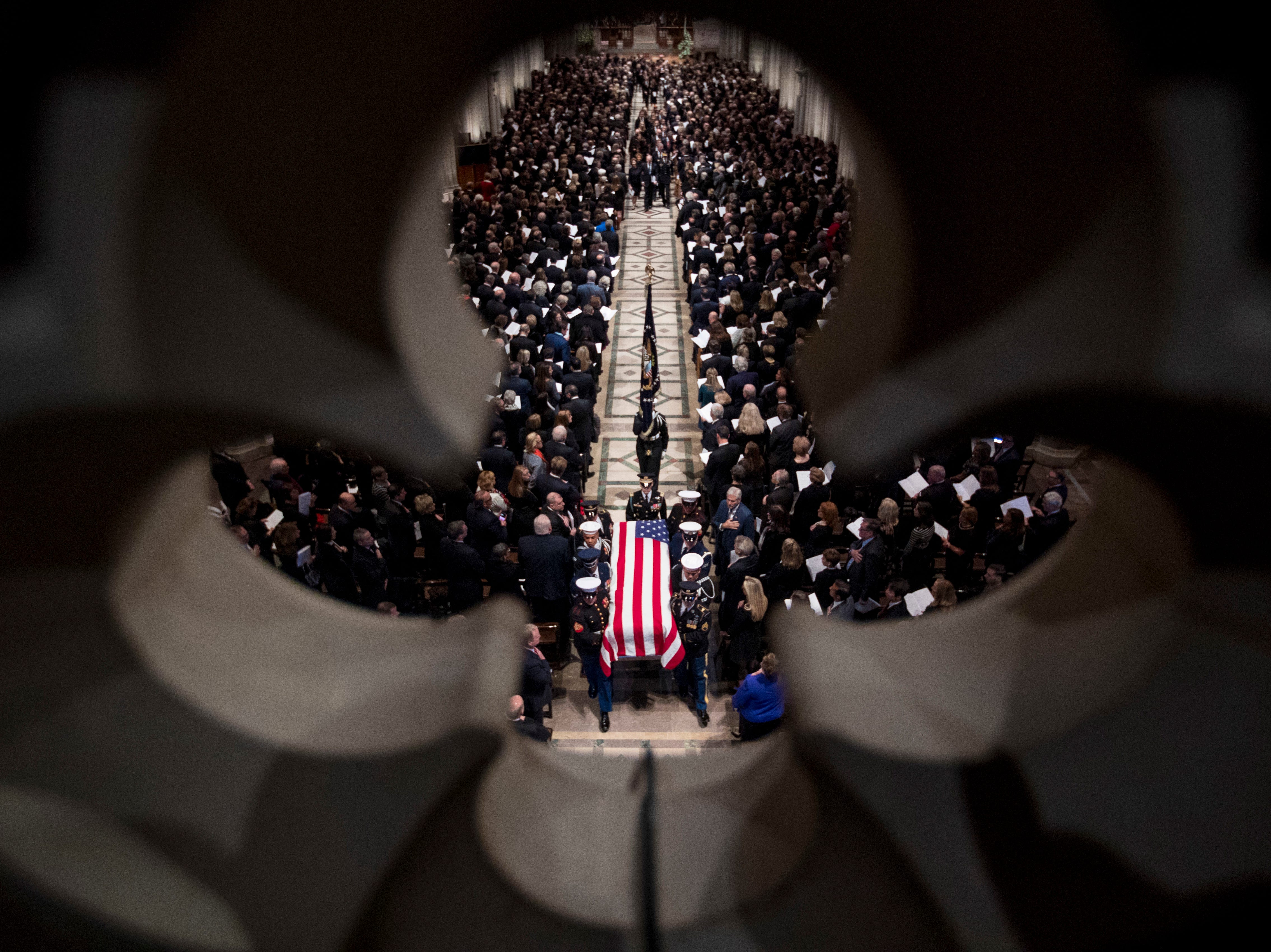 The flag-draped casket of former President George H.W. Bush is carried out by a military honor guard during a State Funeral at the National Cathedral, Wednesday, Dec. 5, 2018, in Washington.