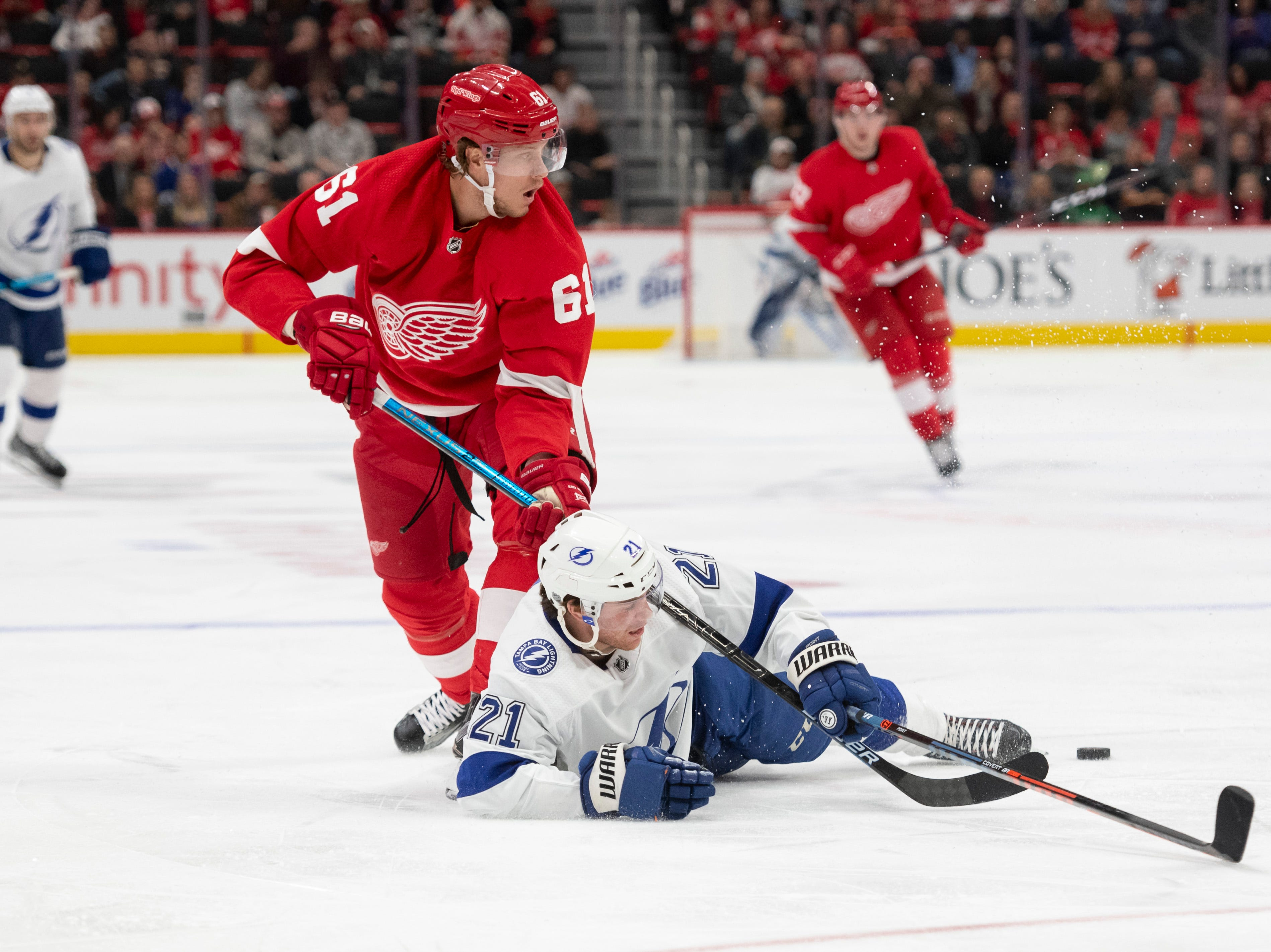 Detroit left wing Jacob De La Rose and Tampa Bay center Brayden Point get tangled up while battling for the puck in the second period.