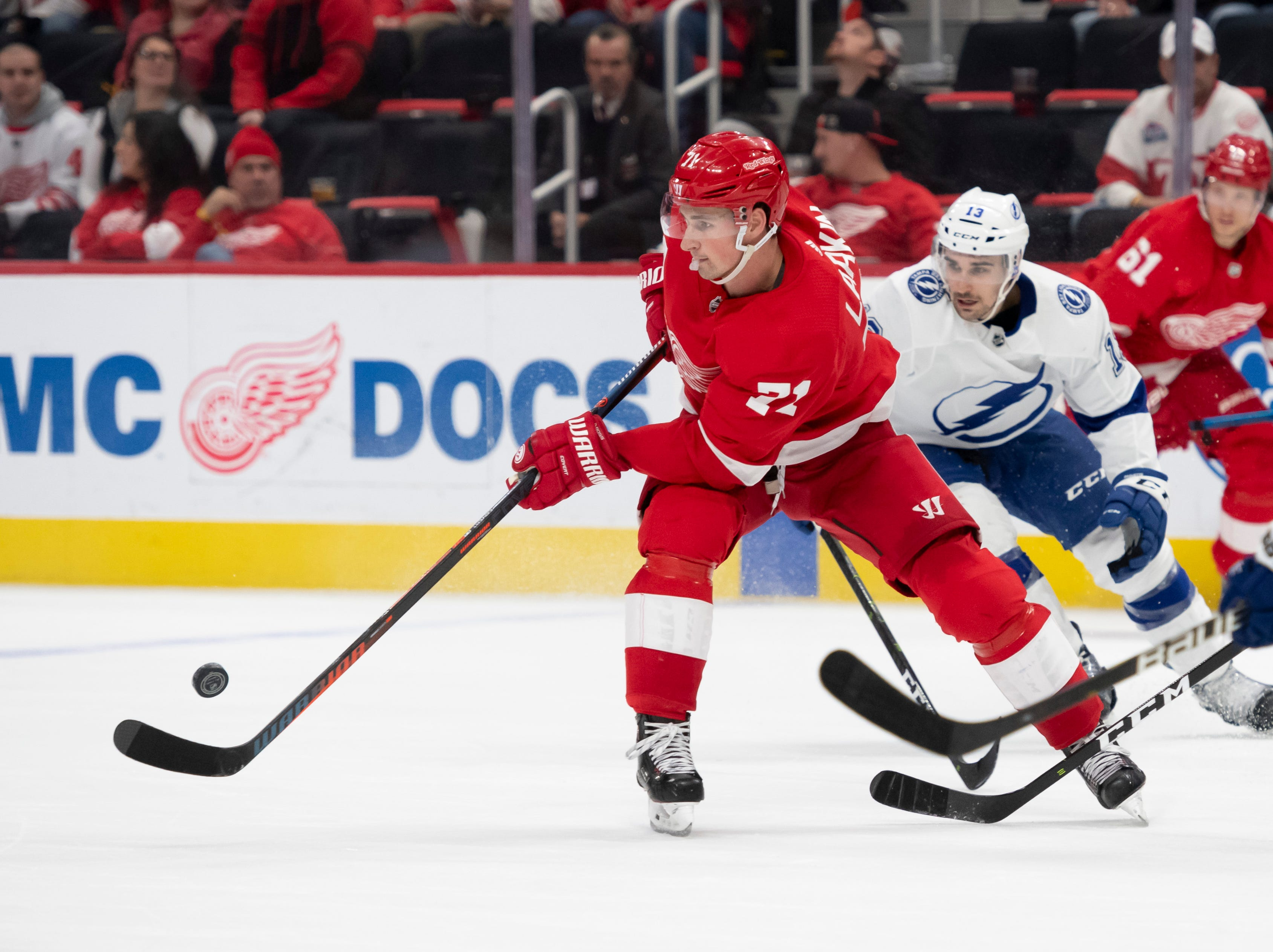Detroit center Dylan Larkin keeps the puck away from Tampa Bay center Cedric Paquette in the third period.