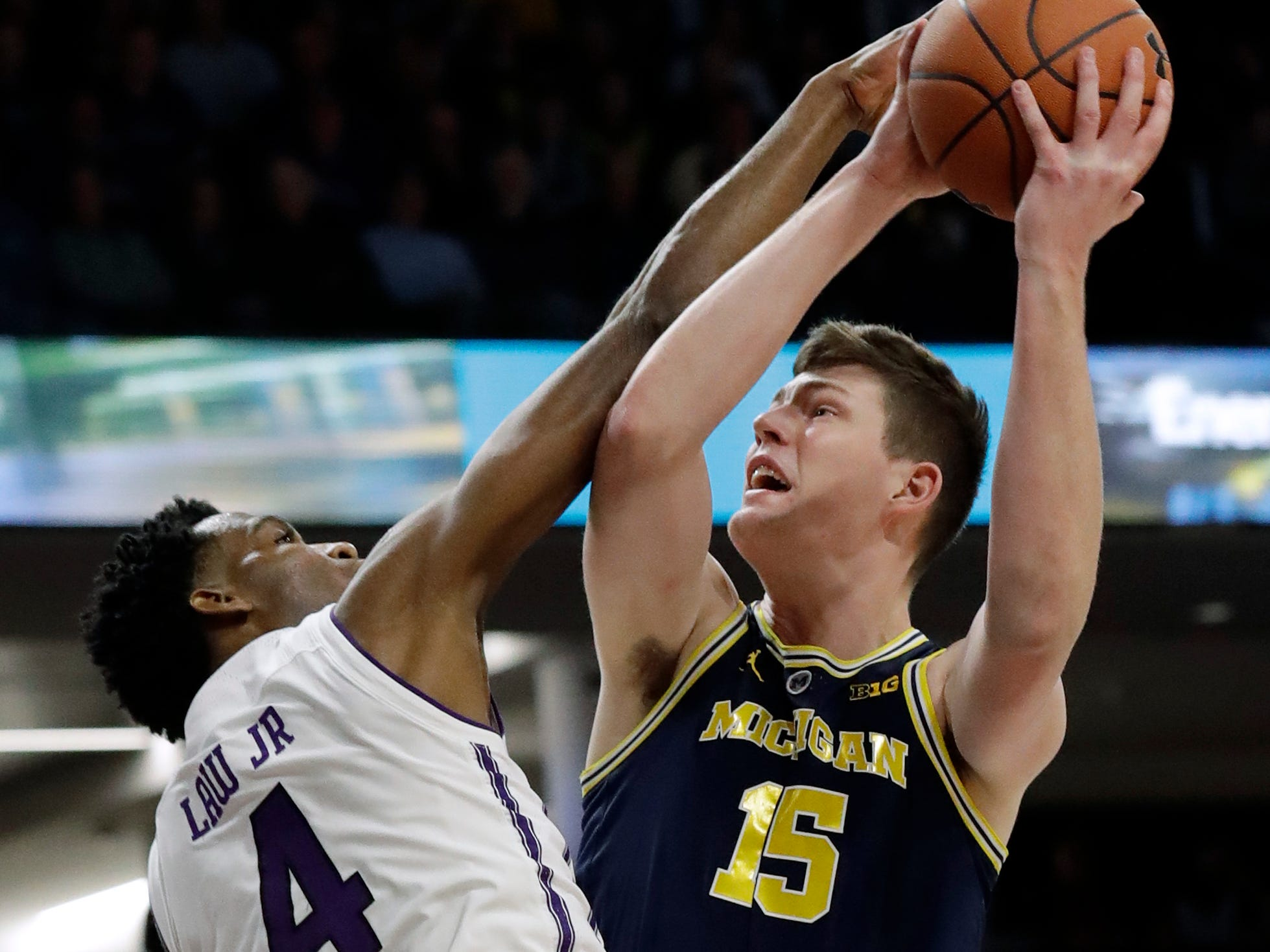Michigan center Jon Teske, right, shoots against Northwestern forward Vic Law during the first half.