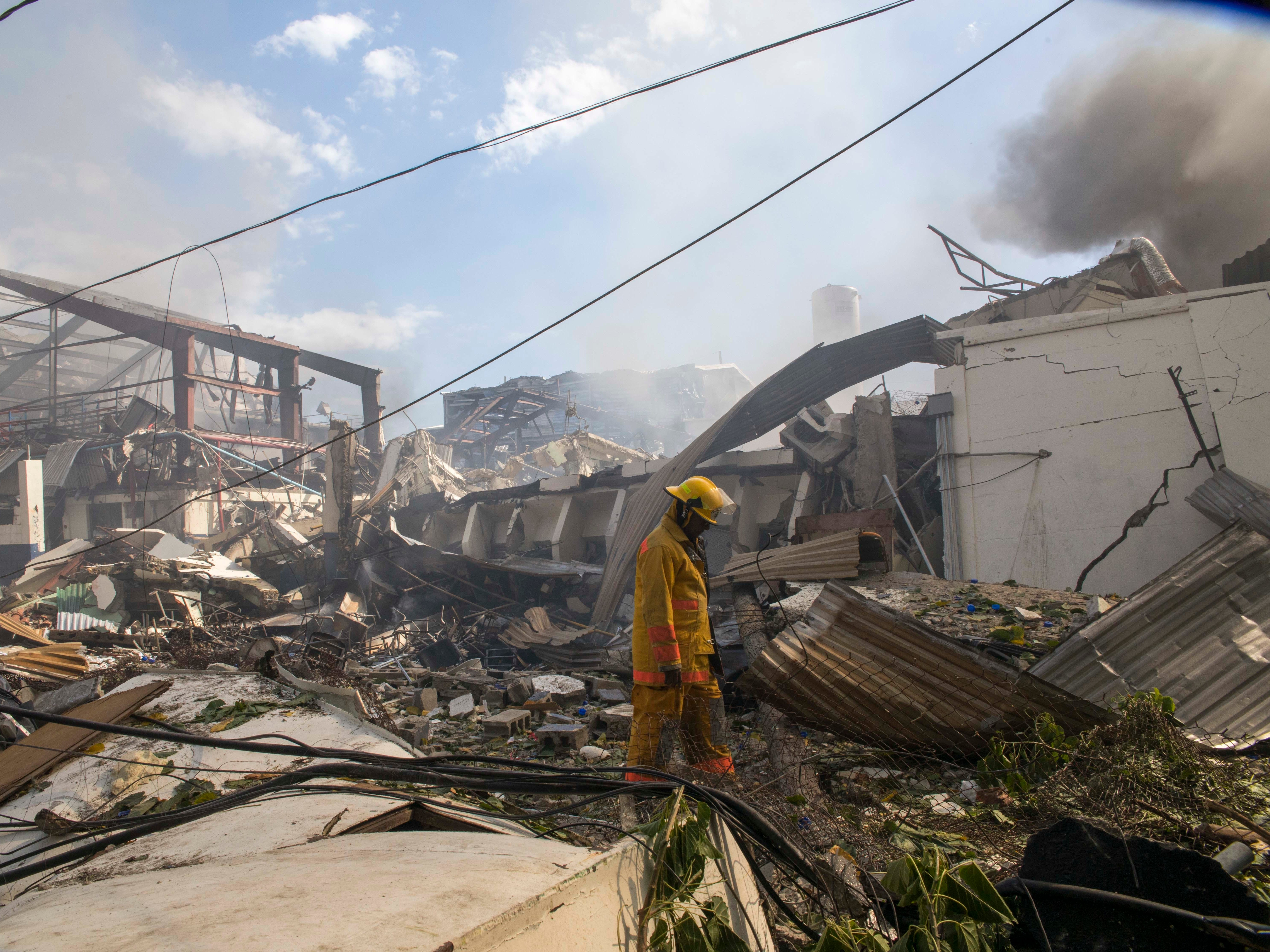 A firefighter walks through debris after an explosion at the Polyplas plant in the Villas Agricolas neighborhood in Santo Domingo, Dominican Republic, Wednesday, Dec. 5, 2018. The mayor told reporters the fire began when a boiler exploded in the early afternoon at the plastics company. Authorities say at least two people have died.