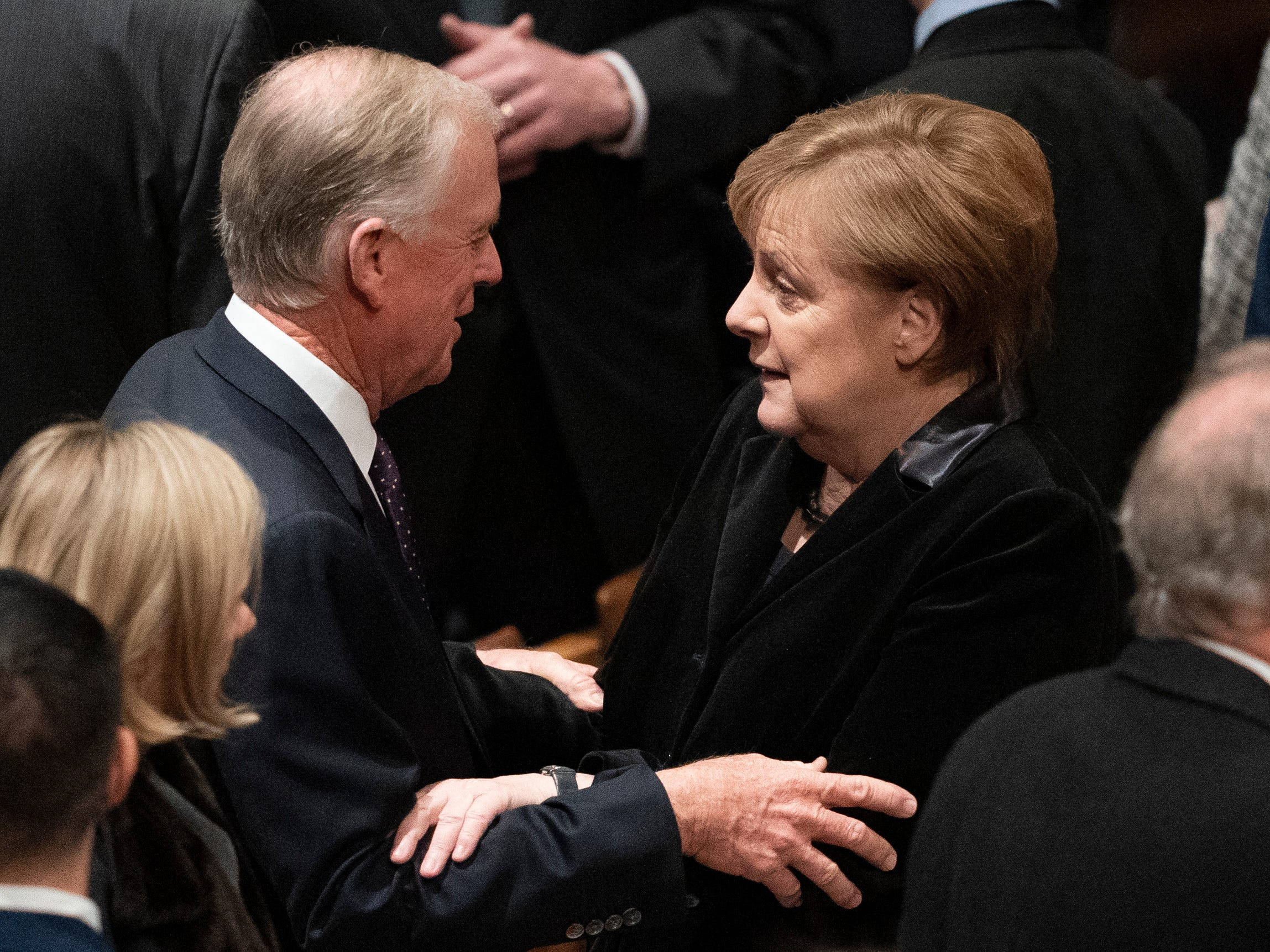 Former Vice President Dan Quayle greets German Chancellor Angela Merkel before the start of the funderal for former President George H.W. Bush at the National Cathedral.