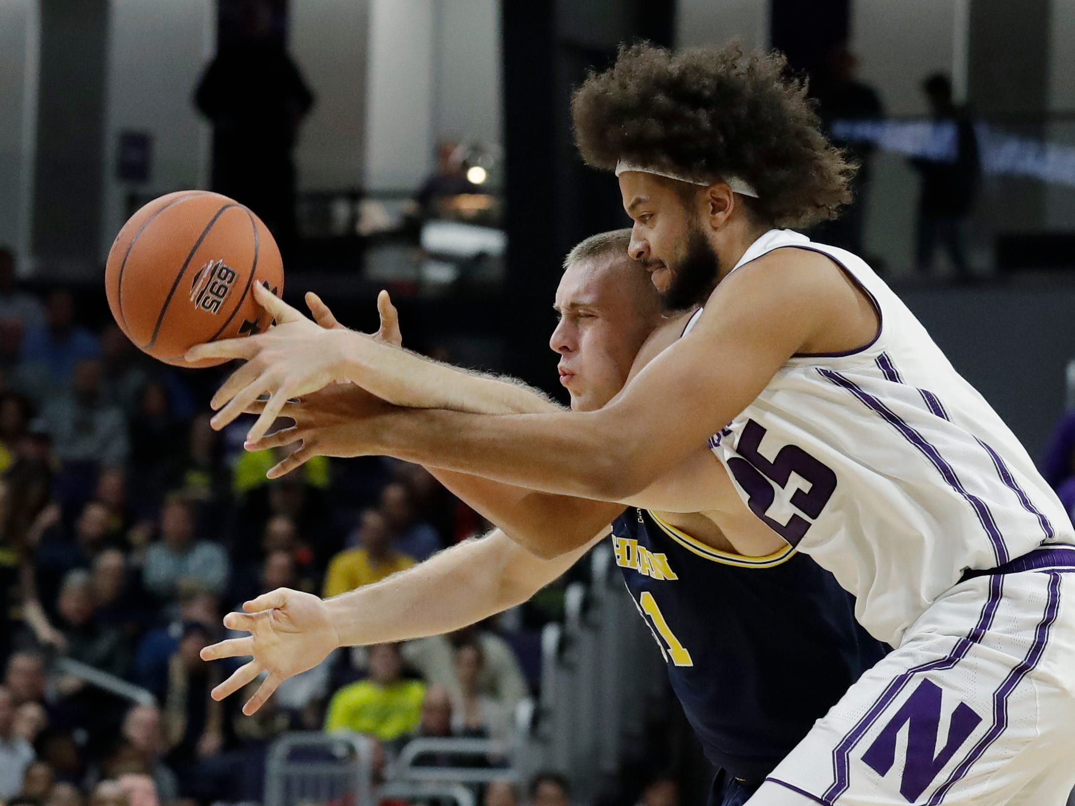 Northwestern center Barret Benson, right, and Michigan forward Austin Davis battle for a loose ball during the first half.