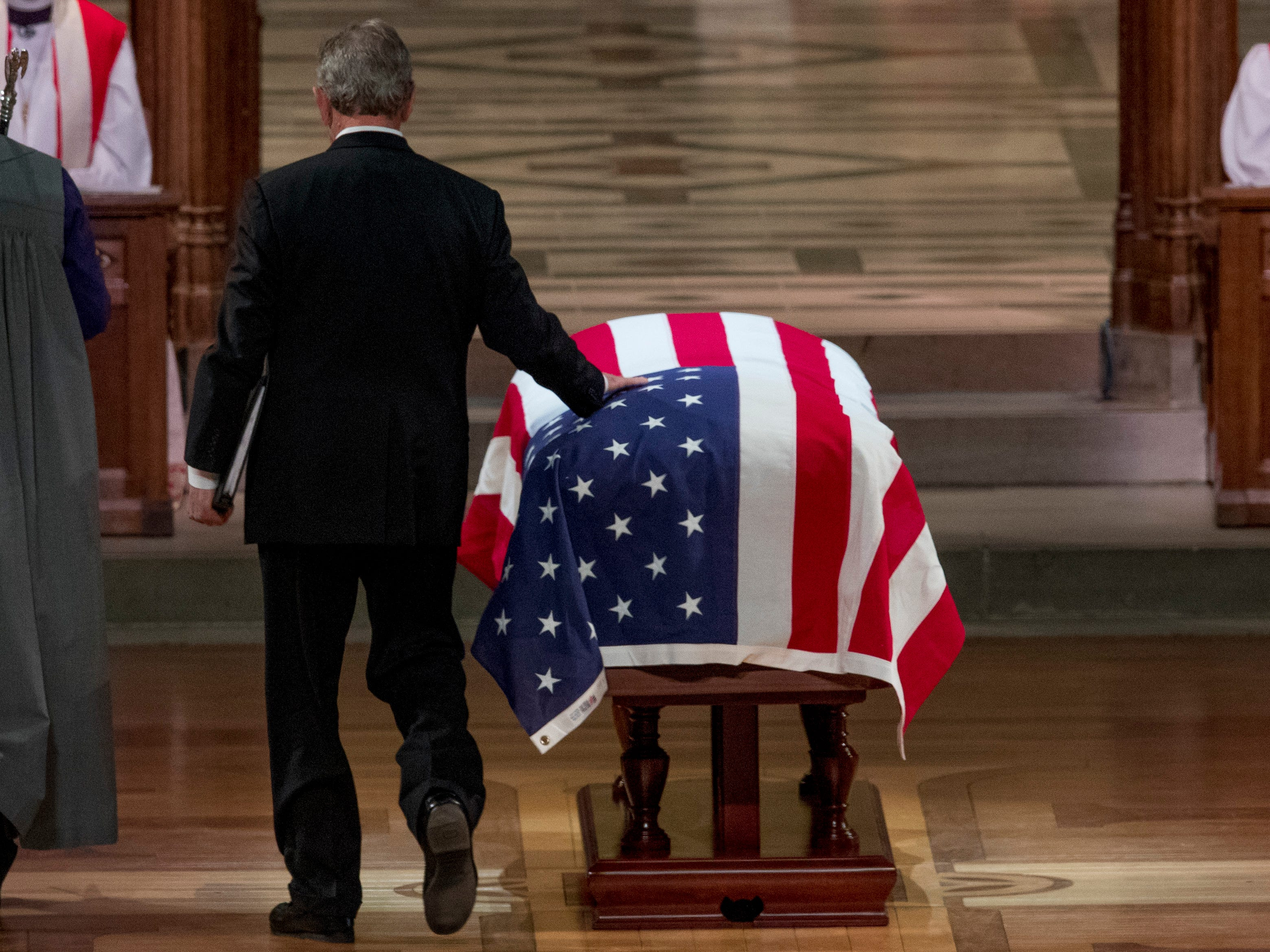 Former President George Bush touches the flag-draped casket of his father as he prepares to speak during the State Funeral at the National Cathedral.