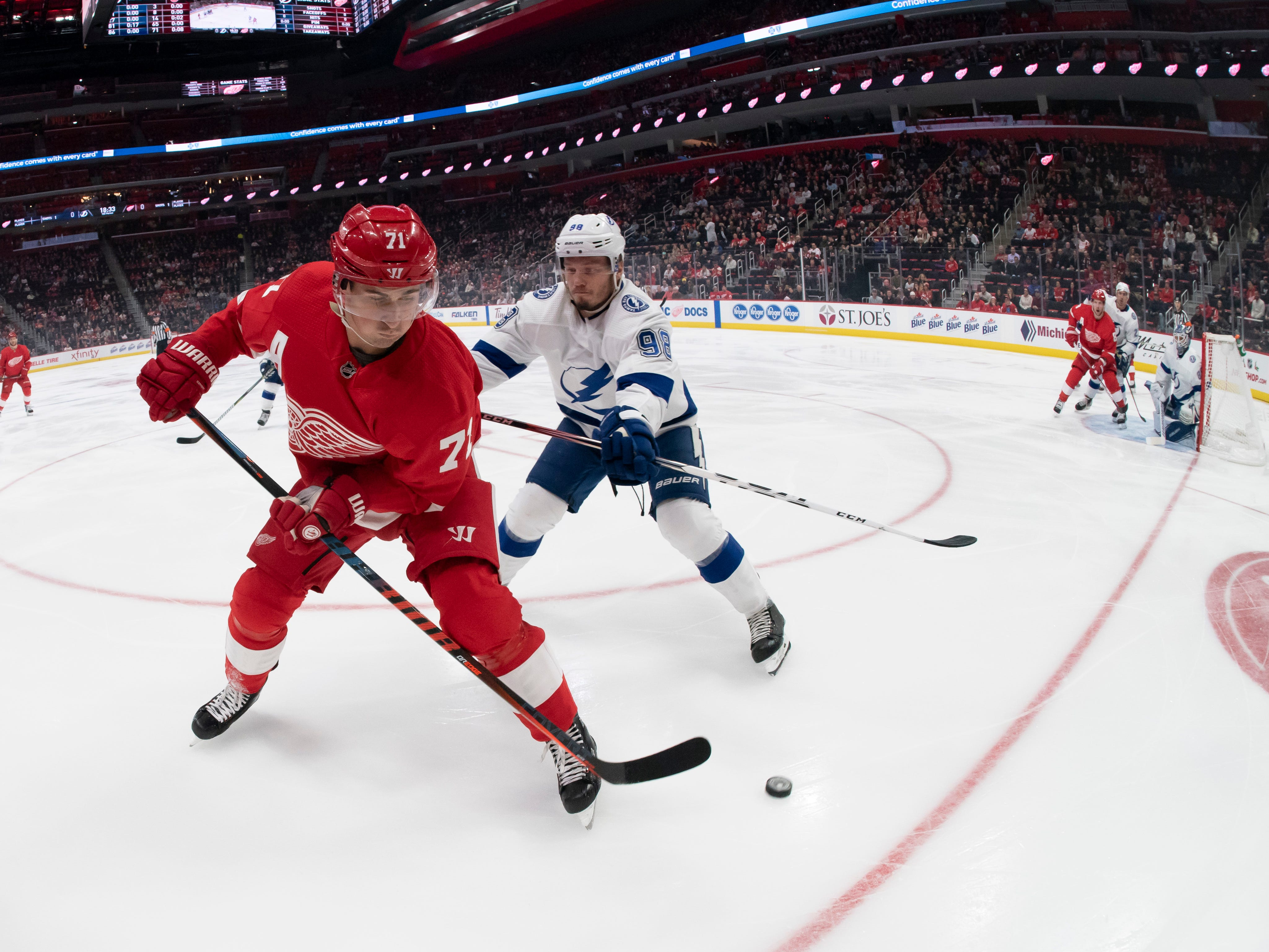 Detroit center Dylan Larkin keeps the puck away from Tampa Bay defenseman Mikhail Sergachev during  first period action of their match at Little Caesars Arena, in Detroit, Tuesday night, December 4, 2018.