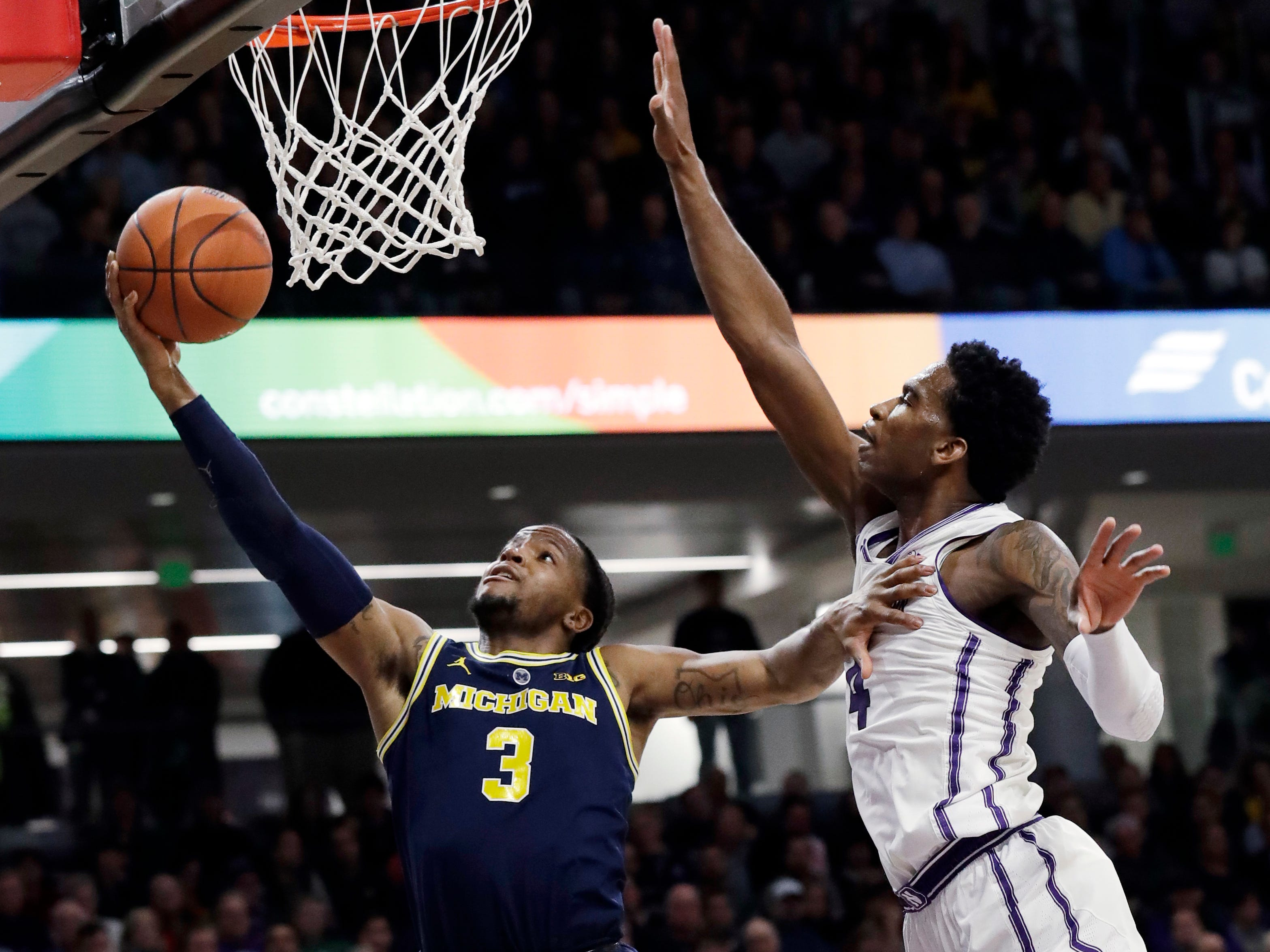 Michigan guard Zavier Simpson, left, shoots against Northwestern forward Vic Law during the first half.