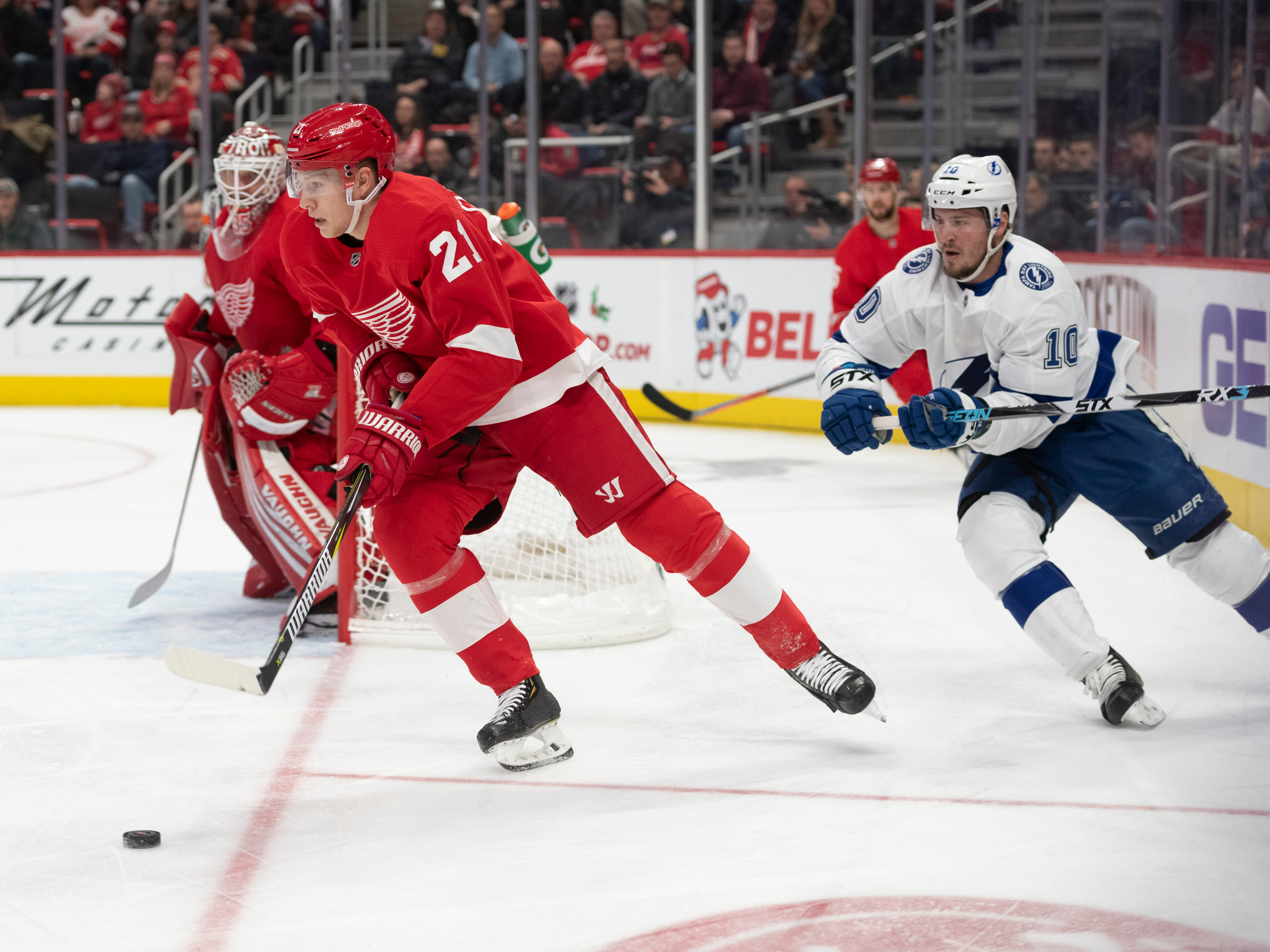 Detroit defenseman Dennis Cholowski keeps the puck away from Tampa Bay center J.T. Miller in the second period.
