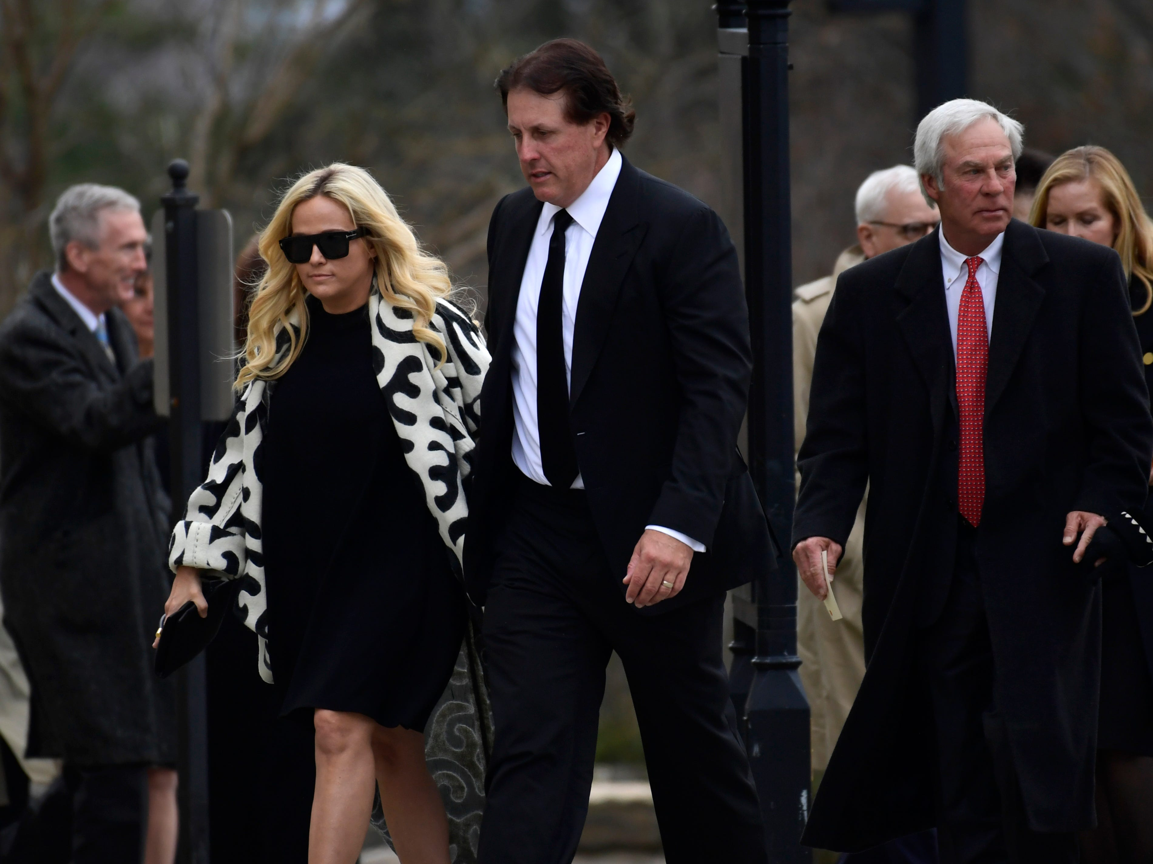 Professional golfer Phil Mickelson, center, arrives for the funeral at the National Cathedral in Washington.