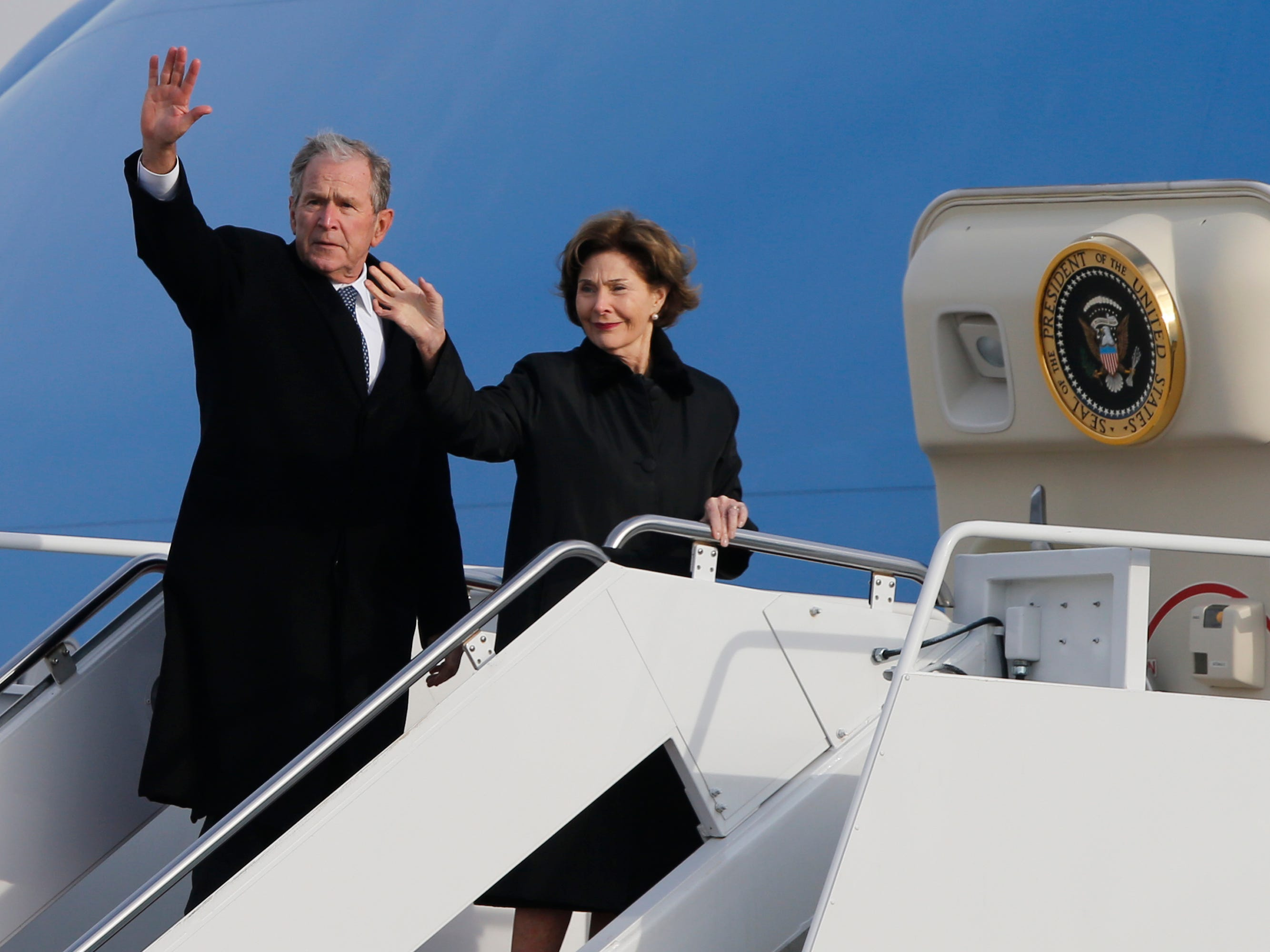 Former President George W. Bush waves to the crowd along with his wife, Laura Bush, after the flag-draped casket of former President George H.W. Bush was carried by a joint services military honor guard to an Air Force jet during a departure ceremony at Andrews Air Force Base, Md.