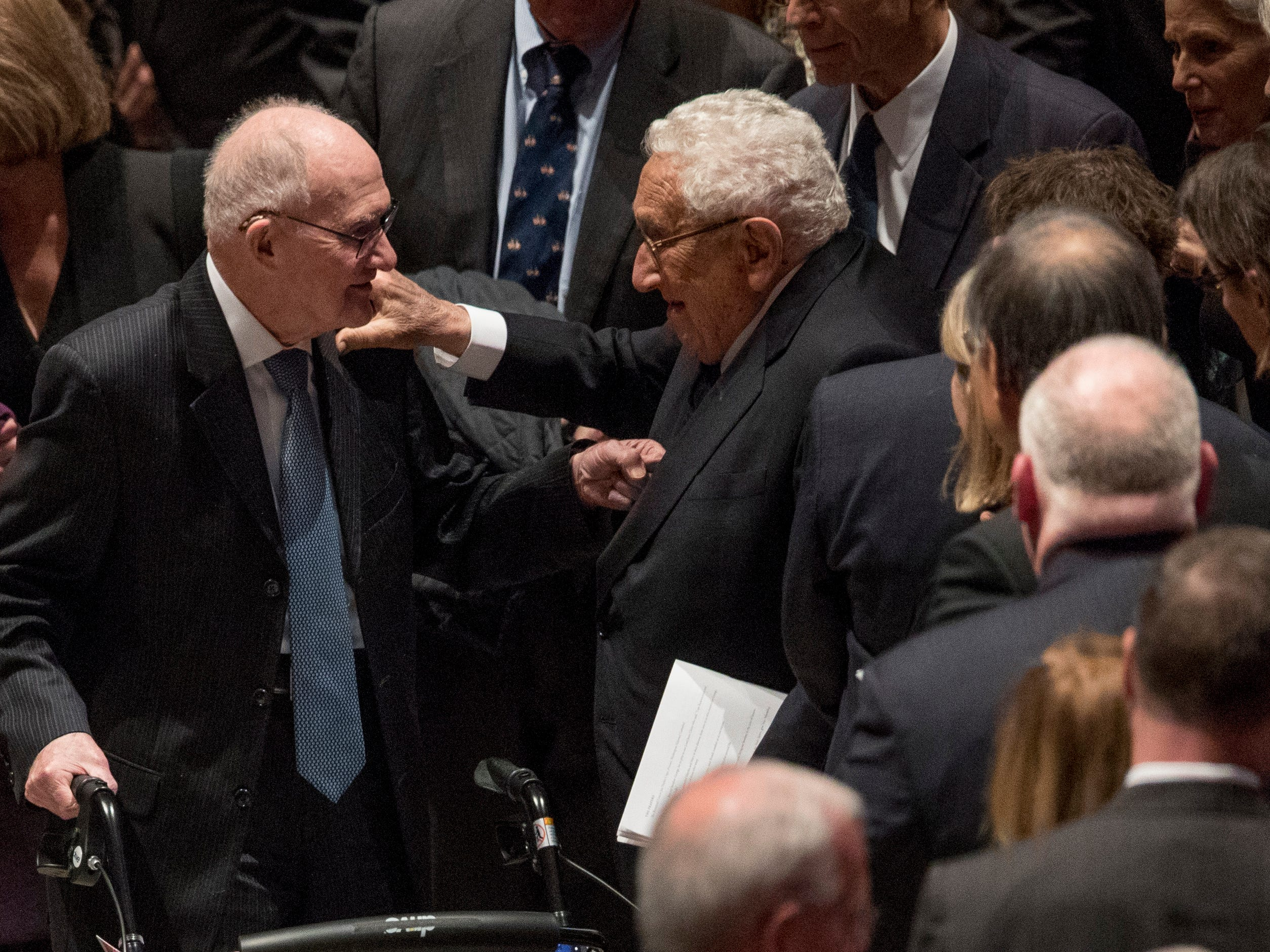 Brent Scowcroft, left, national security adviser for President George H.W. Bush, and former Secretary of State Henry Kissinger exchange greetings following the State Funeral.