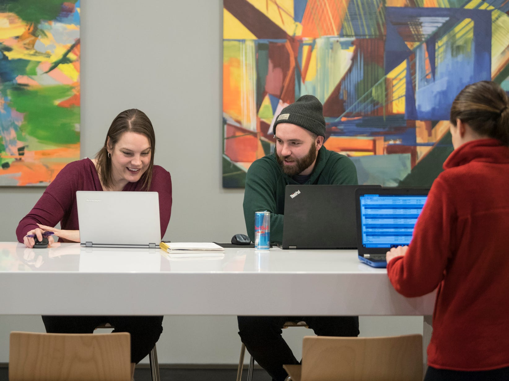 Leslie Wade, from left, and John Pena, both employed by a consulting company called ThoughtFire, chat about a project as Alisa Shelton works remotely for a moving and logistics services company called Alexander's Mobility Service inside the new Cowork Evansville space in downtown Evansville, Ind., Tuesday, Dec. 4, 2018.