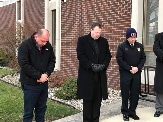 Fremont Mayor Danny Sanchez, left, with pastor Michael Roemmele of St. Ann and St. Joseph parishes, middle, and Fremont Fire Chief Dave Foos share a moment of silence for the late President George H.W. Bush, who died Friday.