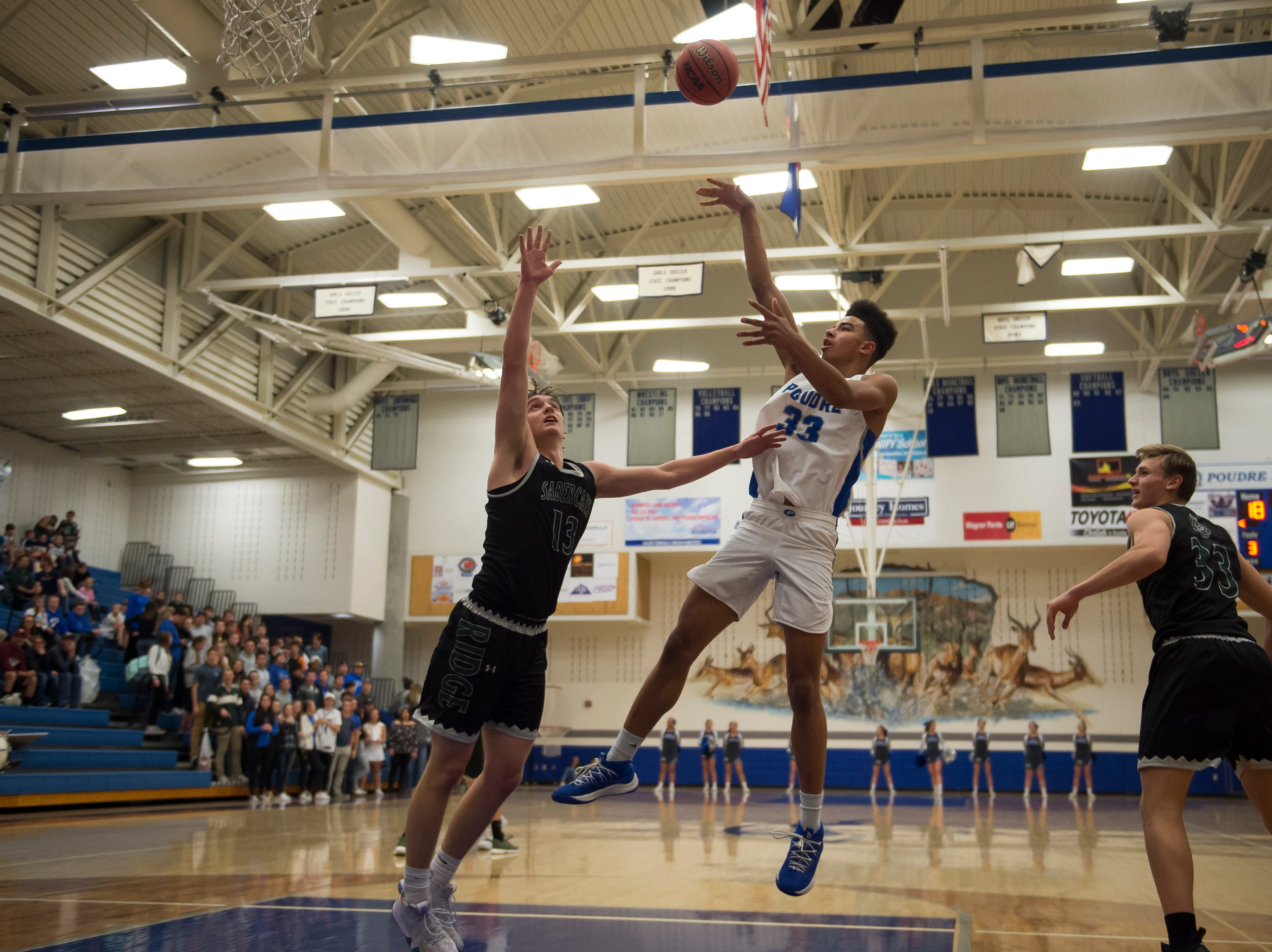 Poudre High School senior Damian Forrest (33) puts a shot up over Fossil Ridge High School senior Holdyn Kawcak (13) on Tuesday, Dec. 4, 2018, at Poudre High School on Fort Collins, Colo.