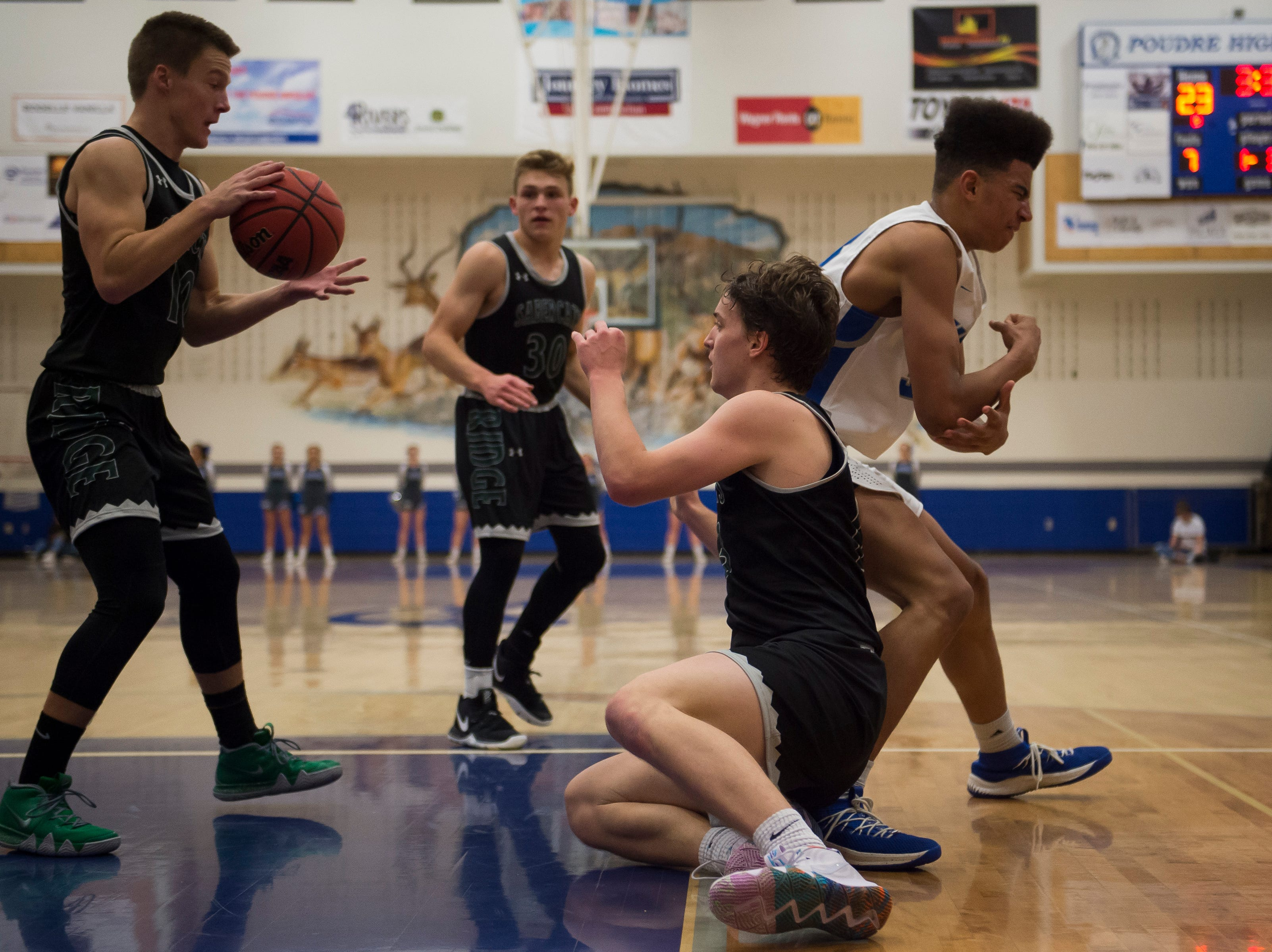 Fossil Ridge High School senior Holdyn Kawcak (13) passes the ball to senior Drew Cornmesser (10) after stealing it away from Poudre High School senior Damian Forrest (33) on Tuesday, Dec. 4, 2018, at Poudre High School on Fort Collins, Colo.