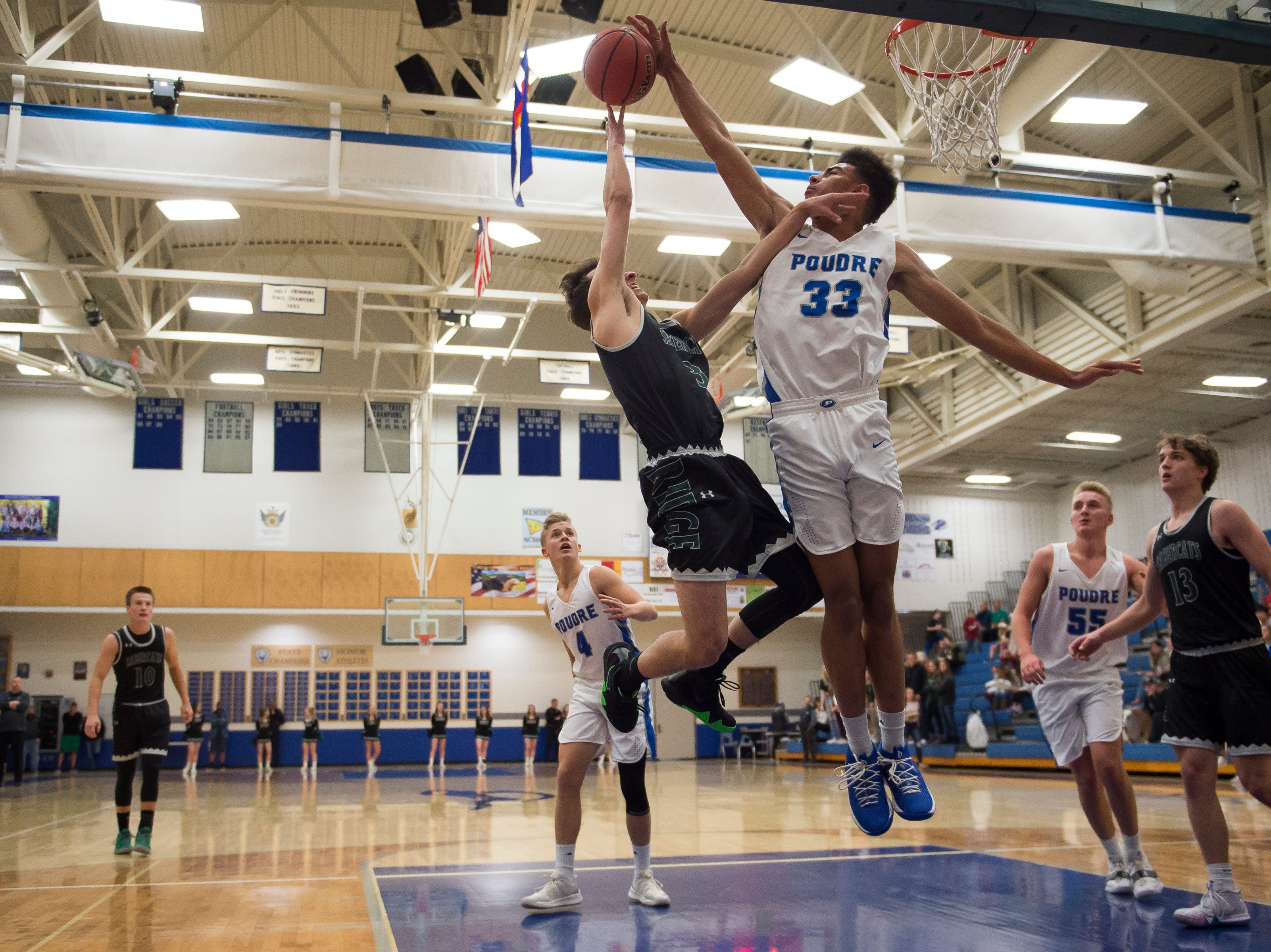 Poudre High School senior Damian Forrest (33) blocks a shot by Fossil Ridge High School senior Tommy Croft (3) on Tuesday, Dec. 4, 2018, at Poudre High School on Fort Collins, Colo.