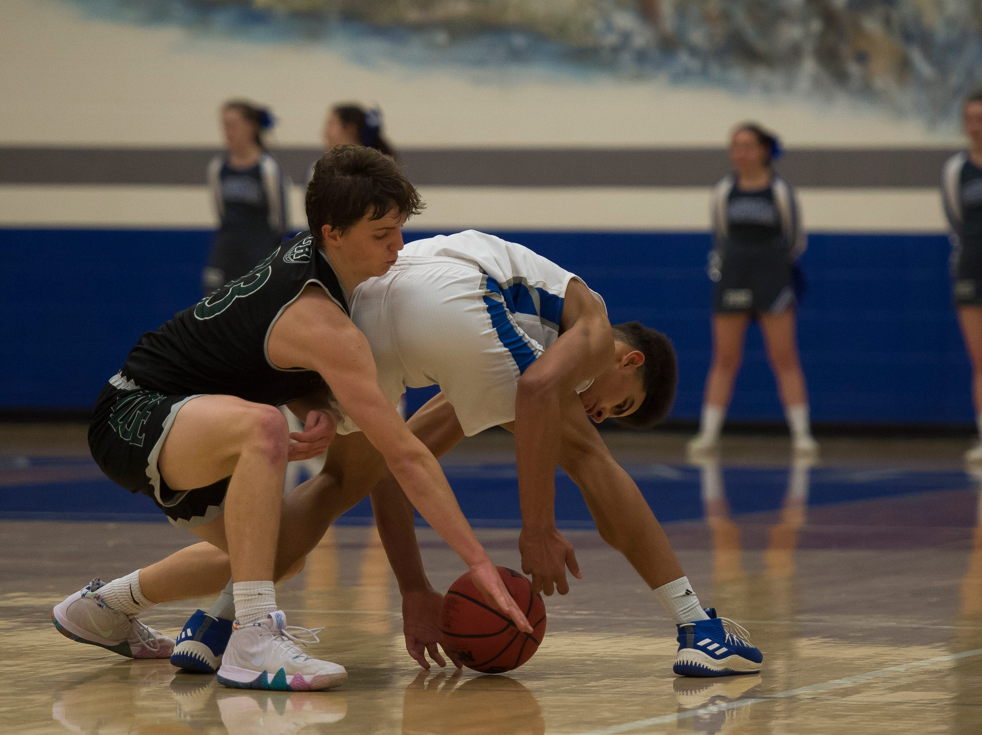 Fossil Ridge High School senior Holdyn Kawcak (13) steals the ball from Poudre High School senior Damian Forrest (33) on Tuesday, Dec. 4, 2018, at Poudre High School on Fort Collins, Colo.