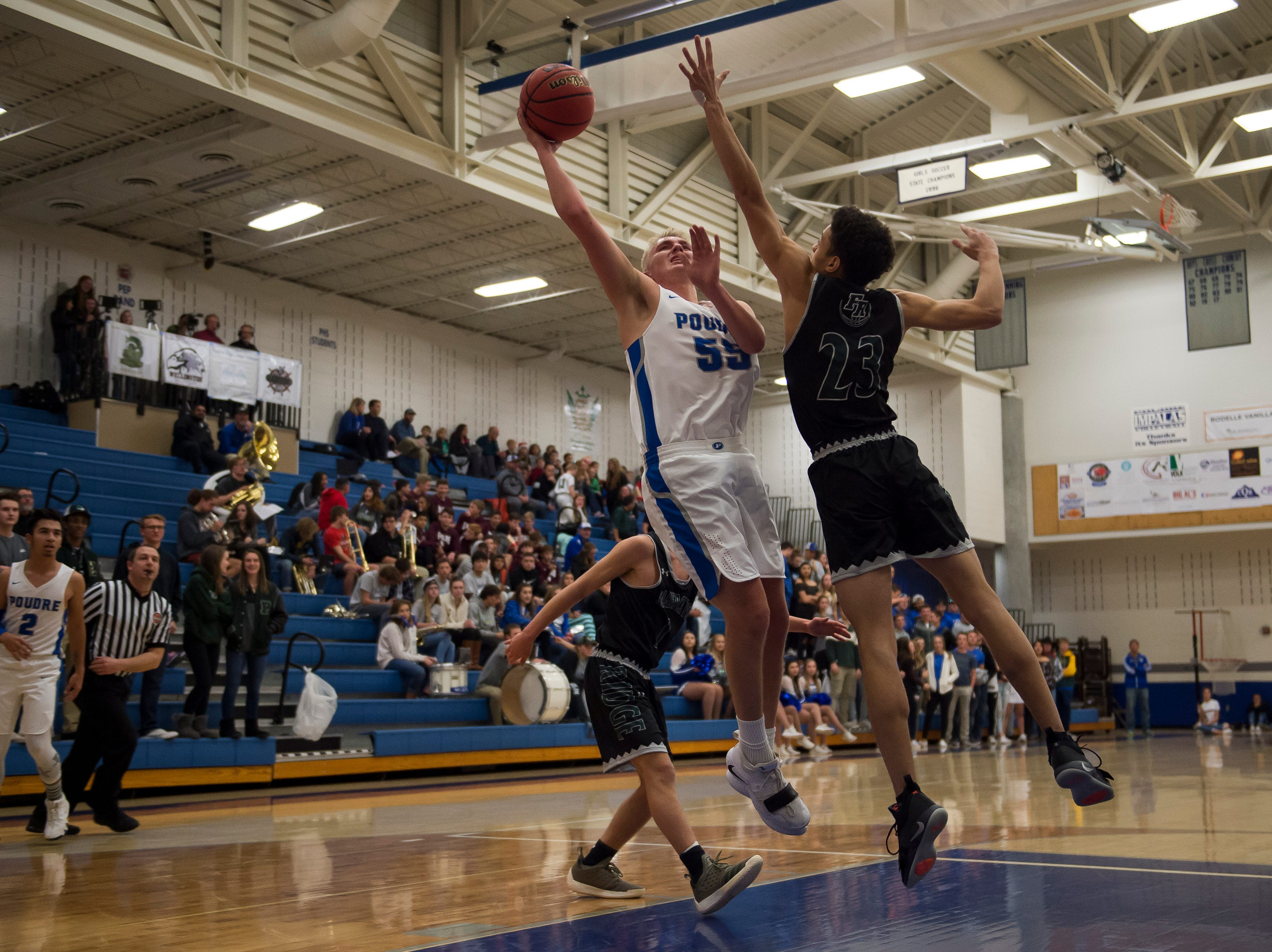 Poudre High School senior Jack Fisher (55) gets a shot past Fossil Ridge High School sophomore Tyce Baldwin (23) on Tuesday, Dec. 4, 2018, at Poudre High School on Fort Collins, Colo.