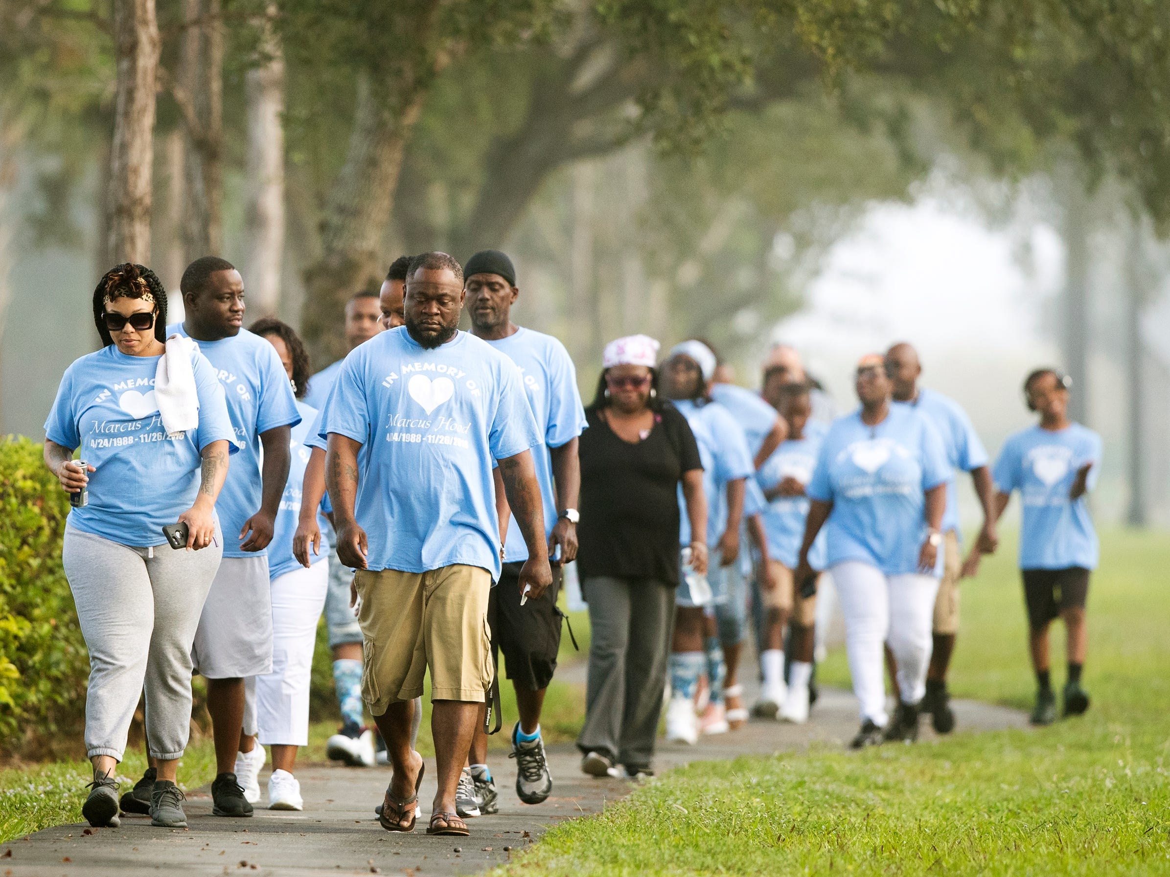 More than 35 family members and friends of Marcus Hood take part in a memorial walk in his honor recently in San Carlos Park. Hood was killed two years ago in a shooting at the Gulf Coast Town Center. The four-mile walk began at the center and ended at Cypress View Drive where emergency personnel found Hood.