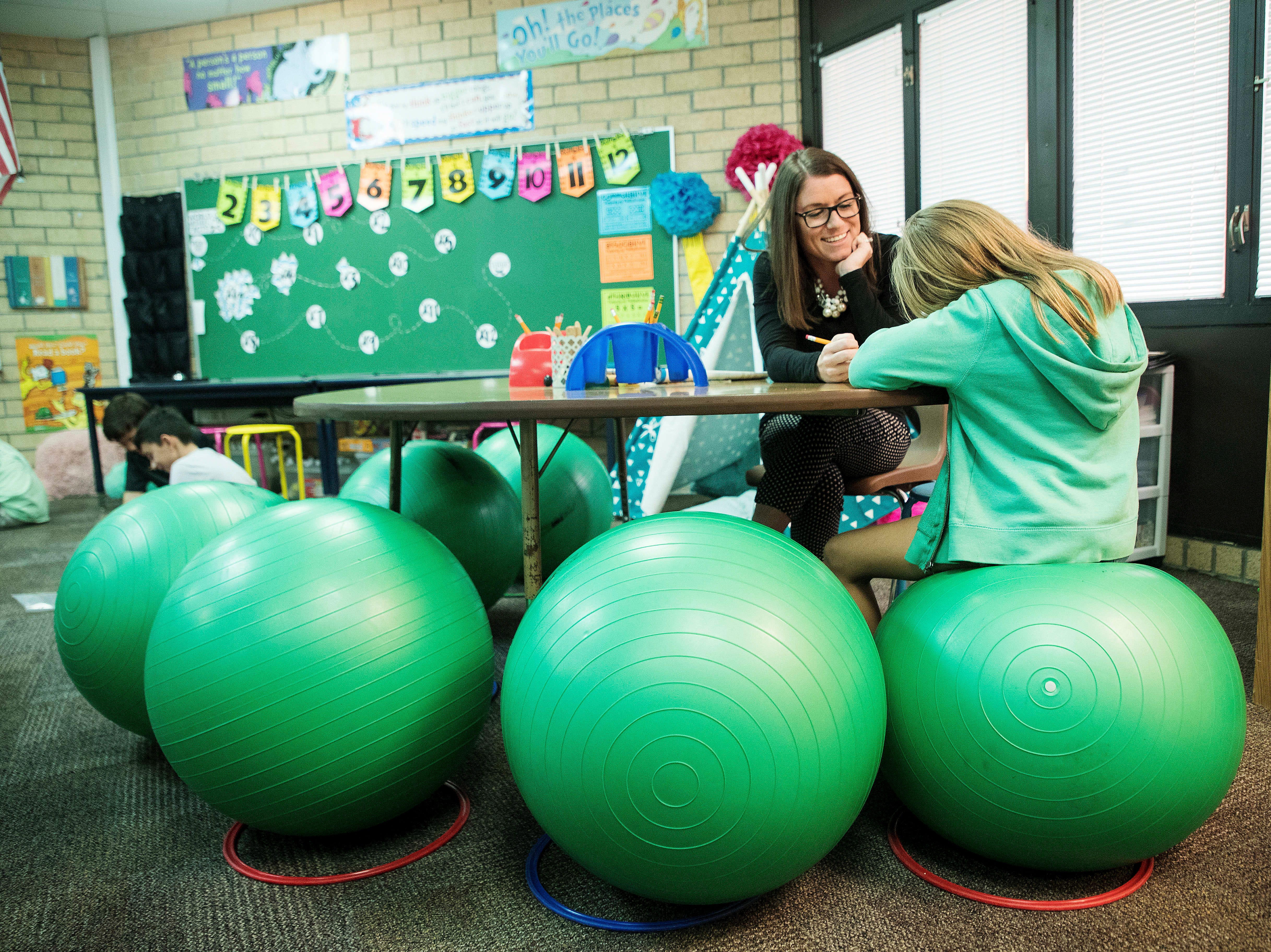 Gulf Elementary school teacher Kristina Gale works with Makenzie Brown, 9. The class uses a flexible seating arrangement which allows students to make choices on where they sit and on what kind of seating they want. Teachers say they have seen an increase in performance.