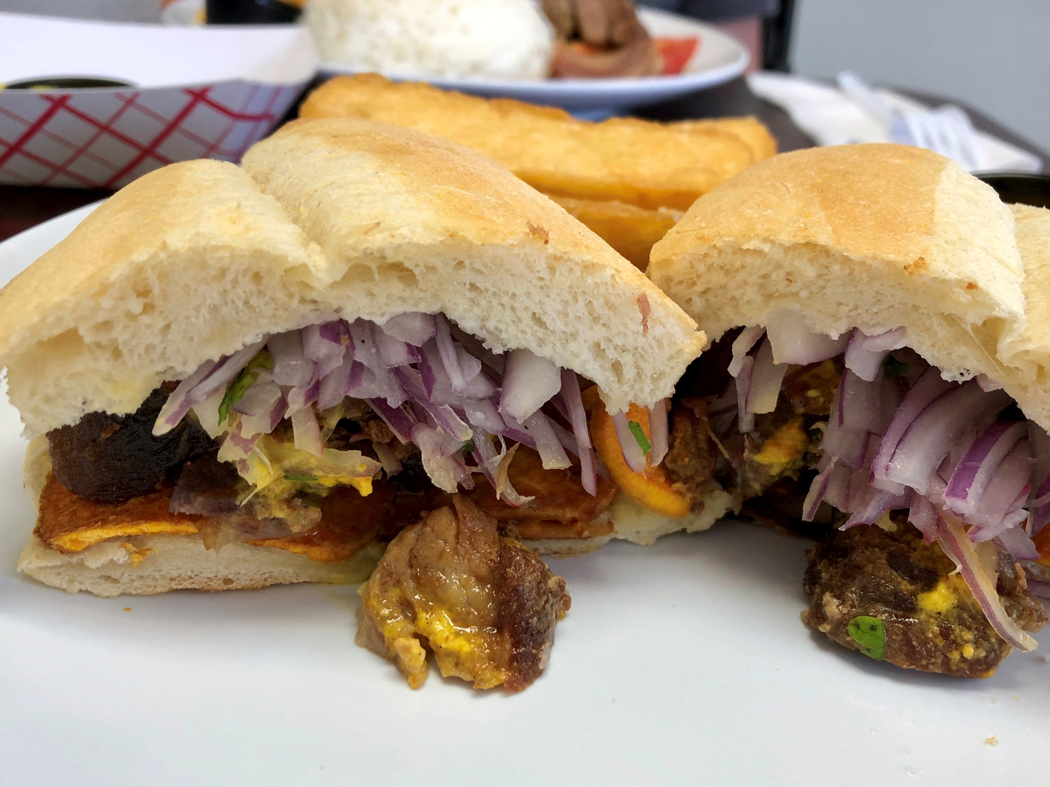 The chicharron sandwich from Renzo's comes with fried pork hunks, thin slices of sweet potato, cilantro and pickles onions. It is a thing of delicious beauty.