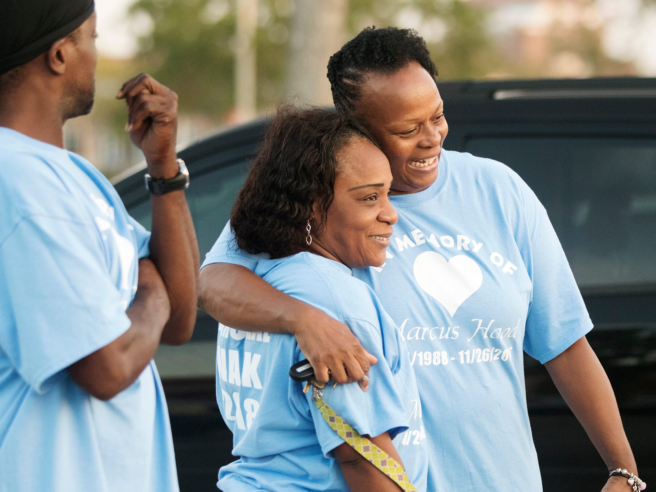 Michelle Taylor, center, joins Renee Perkins on recently at a memorial walk for Perkins' son, Marcus Hood, who was killed two years ago in a shooting at the Gulf Coast Town Center in San Carlos Park. More than 35 of Hood's family members and friends walked four miles from the center to Cypress View Drive where emergency personnel found Hood.