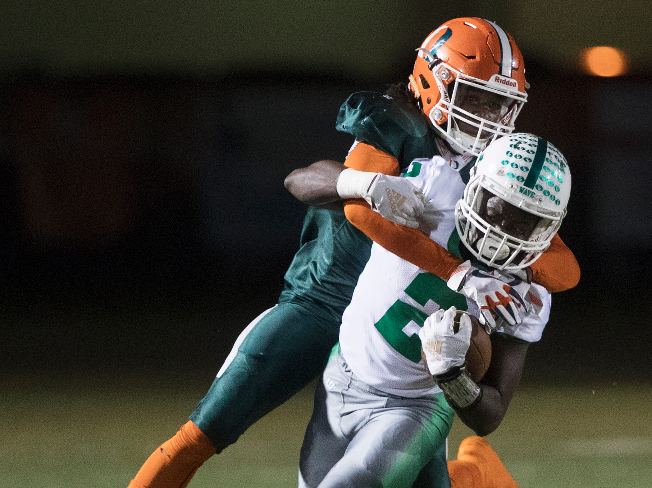 Fort Myers High School's Yasias Young is tackled by DunbarÕs Jeremiah Livingston recently at Dunbar in Fort Myers. Dunbar beat Fort Myers 19-11.