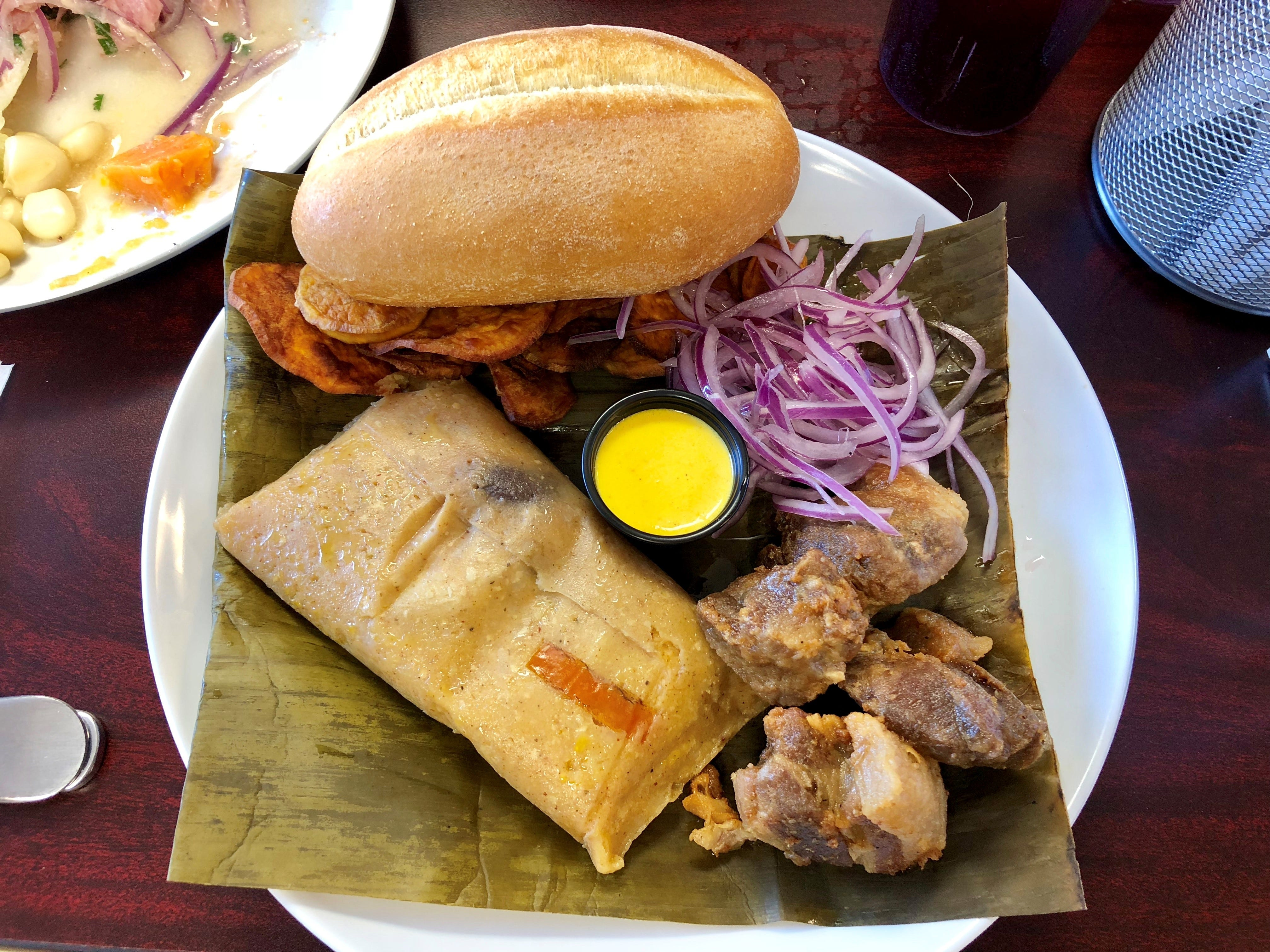 The desayuno Limeno, or Lima-style breakfast, from Renzo's Peruvian Kitchen features chicharron, a tamale, sweet-potato chips and pickled onions.