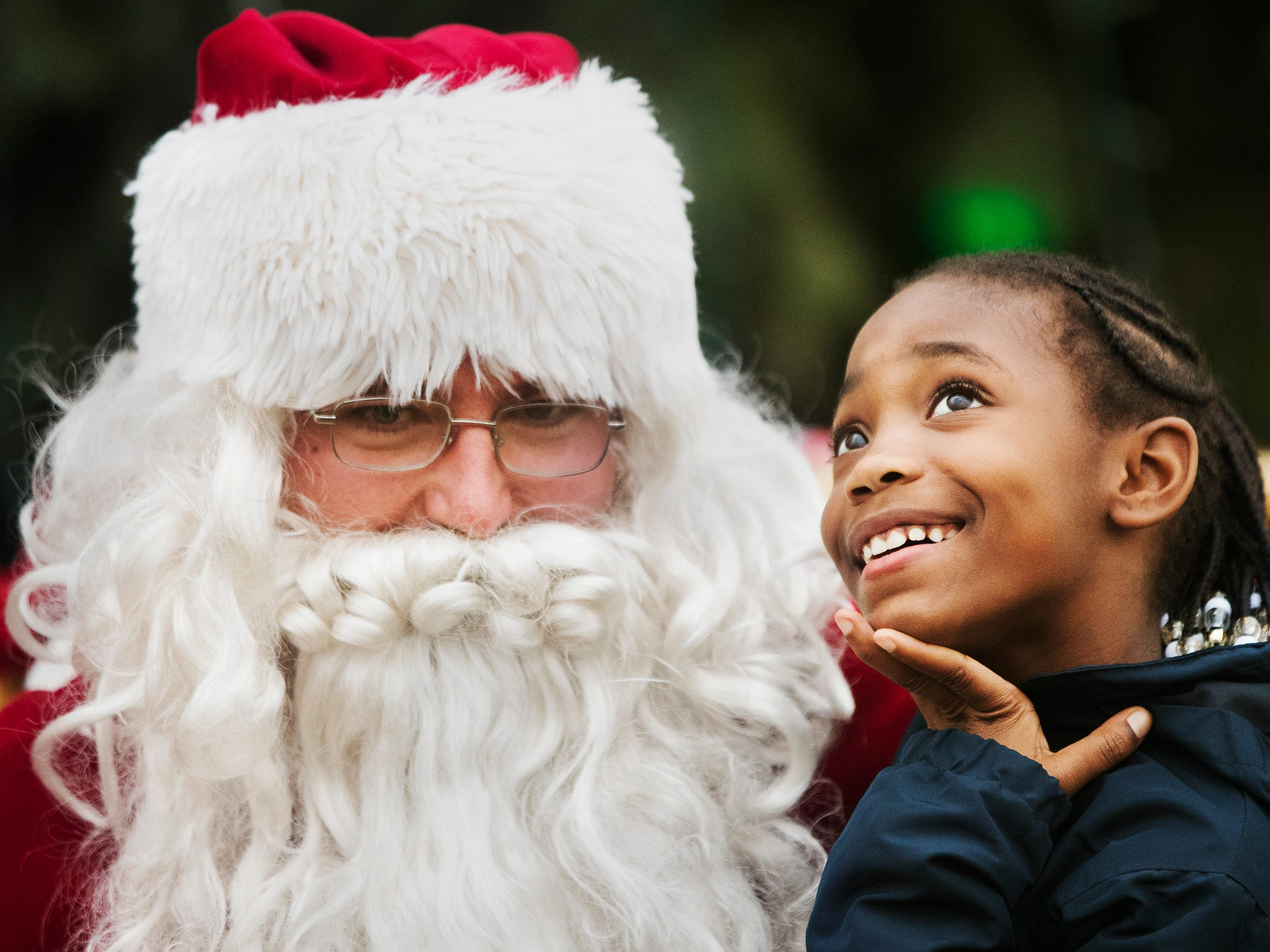 """Books and an iPhone,"" Desiree Bush, 8, tells Santa Claus are what she wants for Christmas recently at the Christmas in the Park event at Centennial Park in downtown Fort Myers. The annual celebration featured kids-activities, live music, a tree lighting and movie."