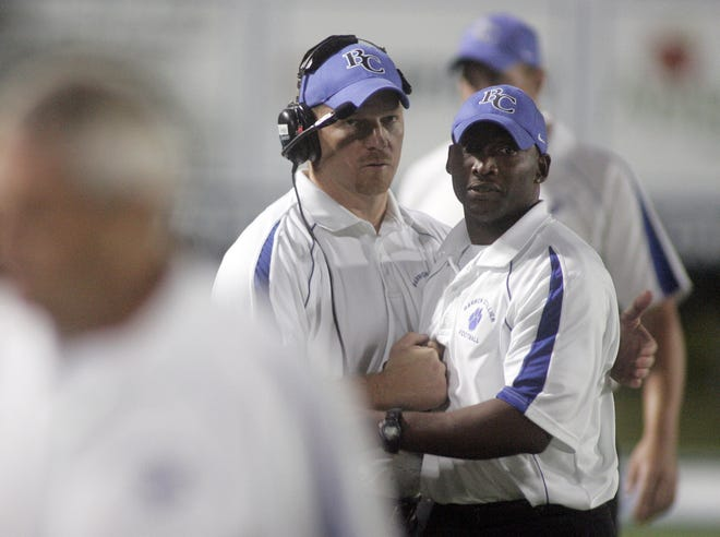 Barron Collier defensive coordinator Johnny Smith, right, gets a hug from head coach Mark Ivey before the start of a game against South Fort Myers on Friday November 20, 2009.