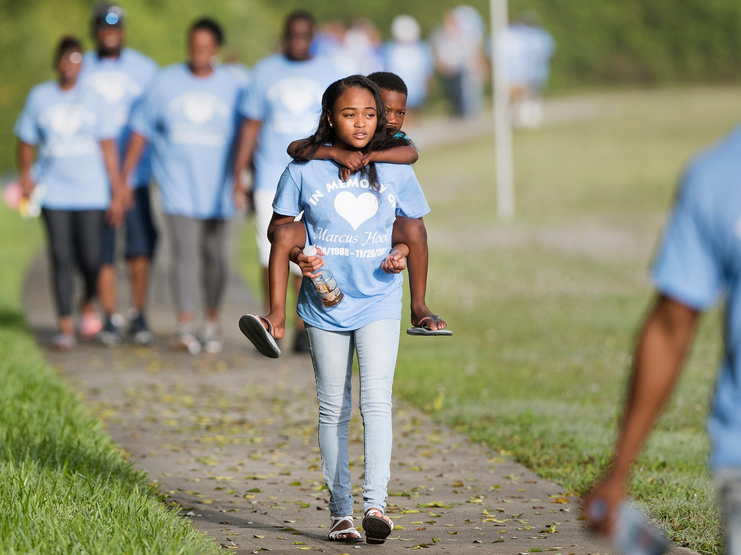 Oshyra Marchman, 18, carries her cousin, Bryson Royal, 5, during a memorial walk recently for Marcus Hood, who was killed two years ago in a shooting at the Gulf Coast Town Center in San Carlos Park. More than 35 of Hood's family members and friends walked four miles from the center to Cypress View Drive where emergency personnel found Hood.