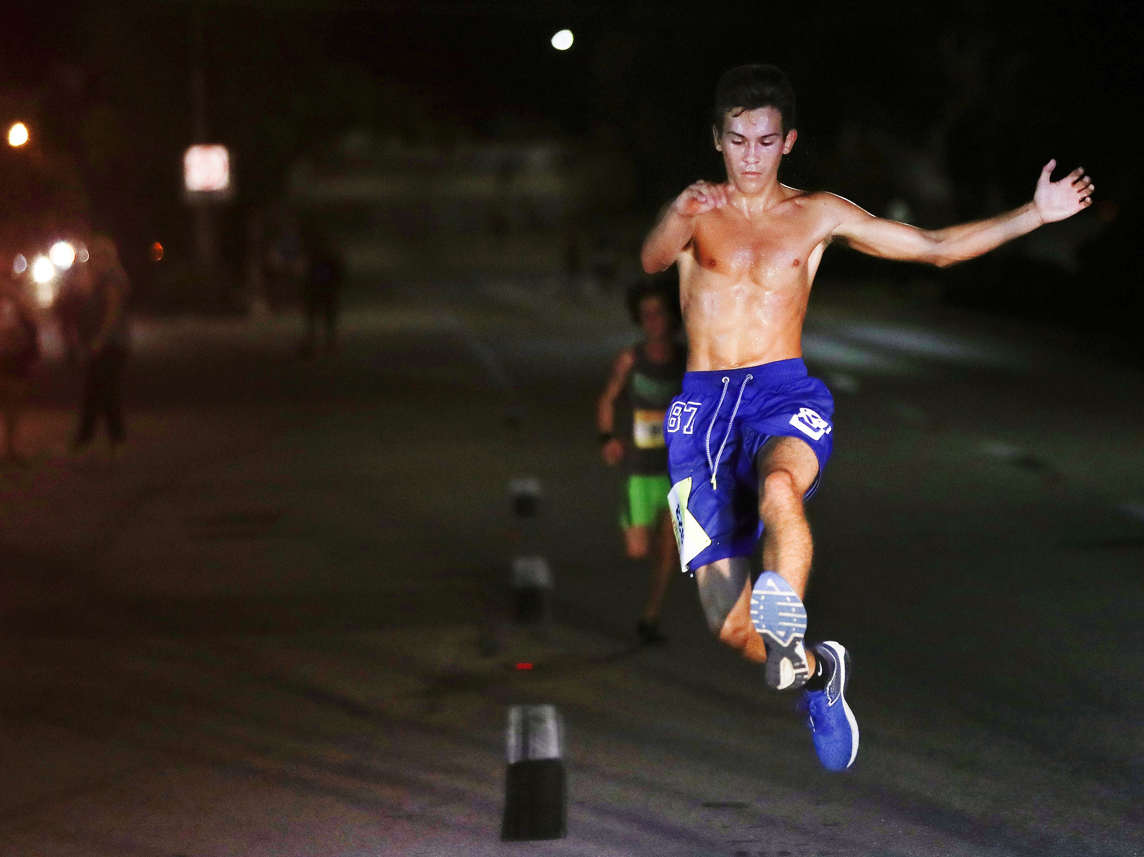 Ryan Hattemer, 15, competes in the Veteran's Day Midpoint Madness 5K recently in Fort Myers. Hattemer was among hundreds of runners and walkers honoring veterans in the annual race that benefits the Fort Myers YMCA.