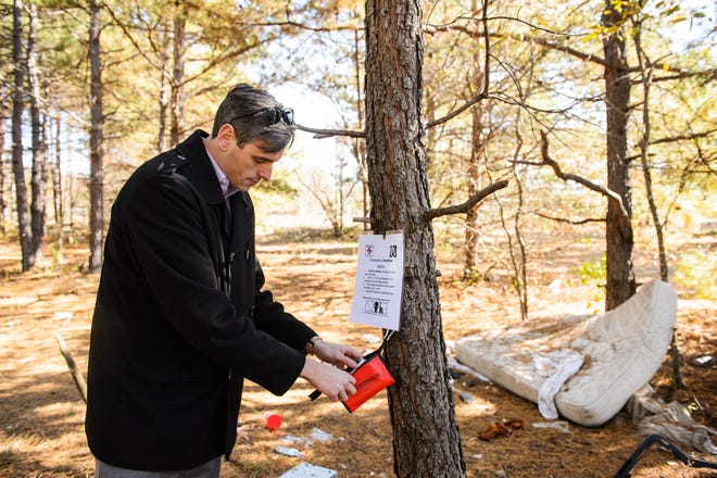 Marc Burrows of Challenges Inc. sets up a naloxone station in a forested area in Greenville on Tuesday, Nov. 27, 2018. Burrows started building these stations in an attempt to prevent overdose deaths in areas where opioid users might not have immediate access to the life-saving drug or are away from bystanders who could call 911.