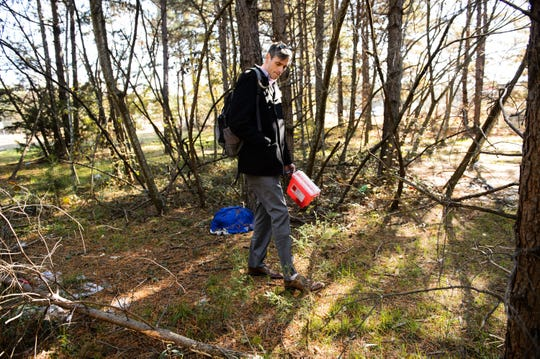 Marc Burrows walks through a wooded area in Greenville to look for a spot to set up a naloxone station on Tuesday, Nov. 27, 2018.