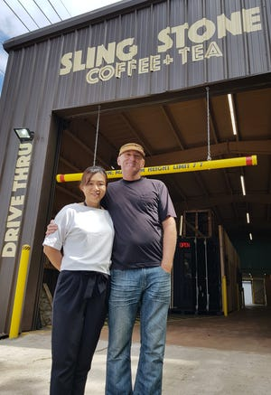 "Entrepreneurs Hiroko and Peter Walls stand in front of their second drive-thru coffee shop along Marine Drive in East Agana. Sling Stone's ""warehouse"" location will be holding its grand opening on Dec. 15."