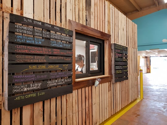 """Inside the repurposed warehouse, drivers are treated to a colorful menu offering unique coffee options, like the strong """"flat white"""" coffee that is popular in Australia and New Zealand, as well as a variety of signature frappes and smoothies."""