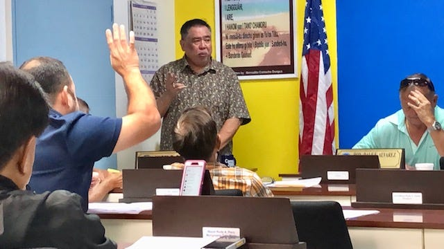 Mayors Council of Guam Executive Director Angel Sablan, standing, addresses village mayors while Sinajana Mayor Robert Hoffman raises his hand during a meeting on Wednesday. Hoffman and Sablan said the mayors' council office will be returning to Adelup next year.
